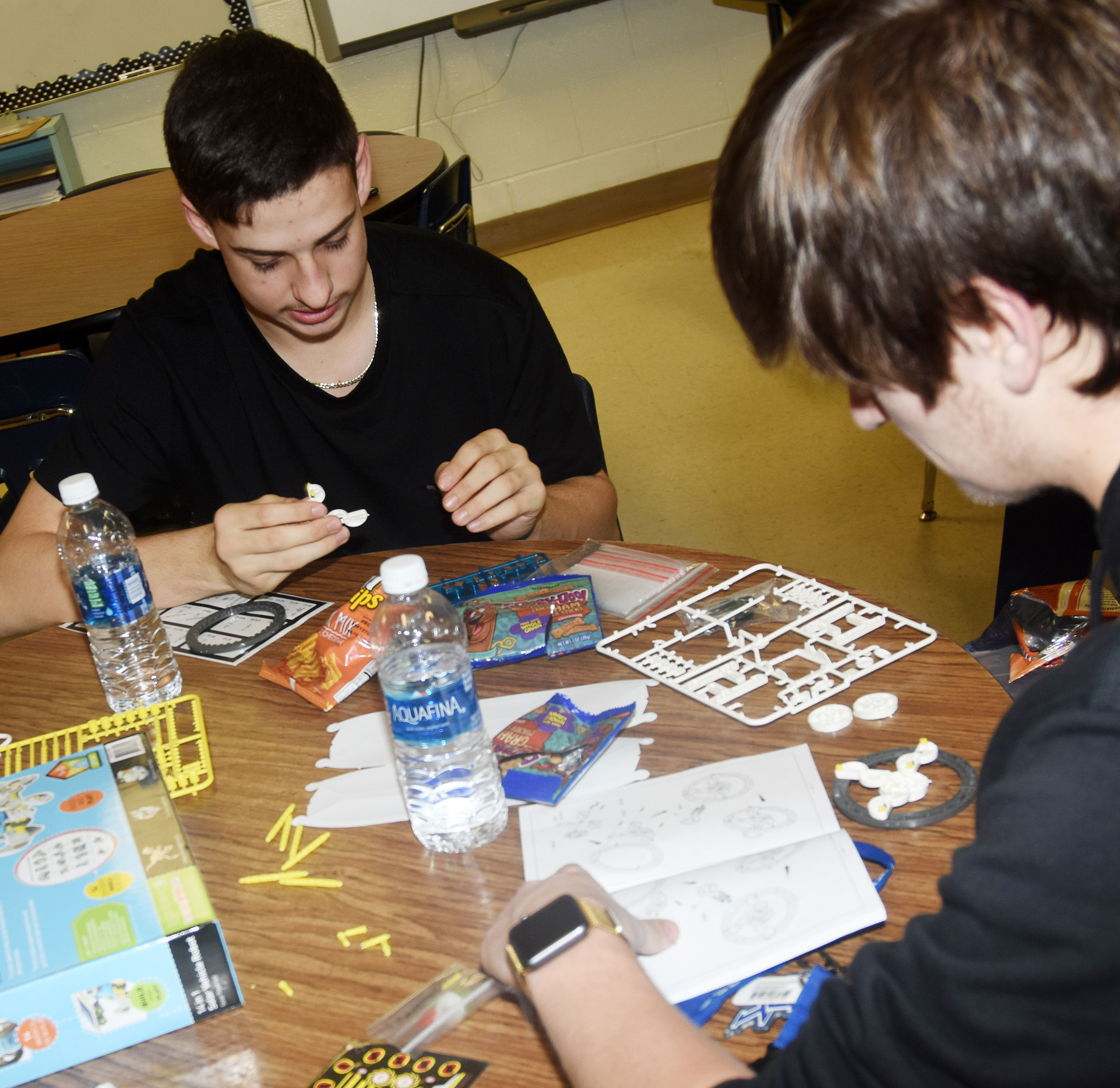 CHS freshman John Orberson, at left, and junior Myles Murrell work together to build a solar vehicle robot.