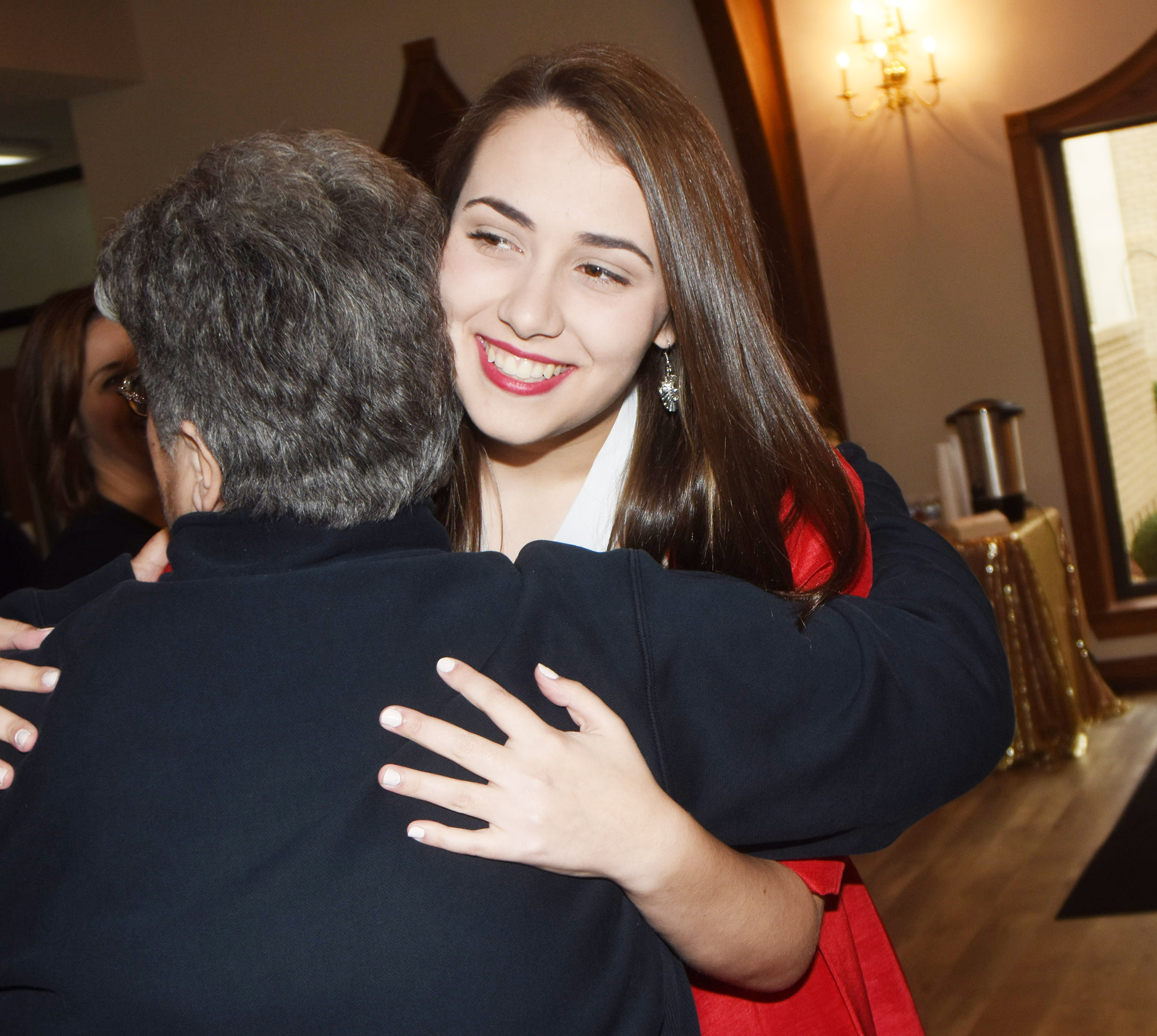CHS senior Elizabeth Sullivan receives a hug at a reception hosted in her honor as she prepares to participate in the Kentucky DYW program. The state program is Jan. 11 and 12 in Lexington.