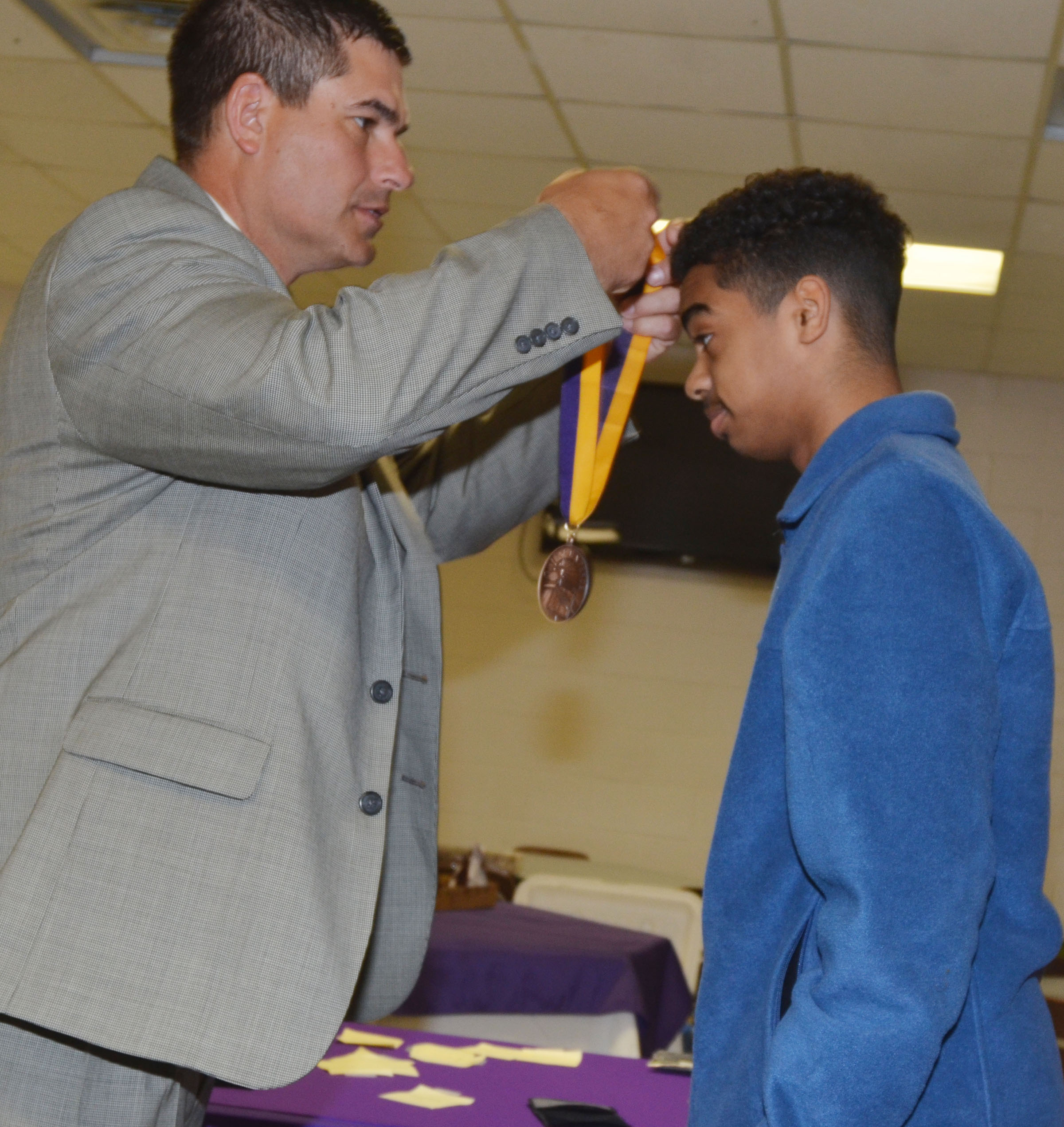 CHS Principal Kirby Smith gives sophomore Davon Cecil his bronze medallion.