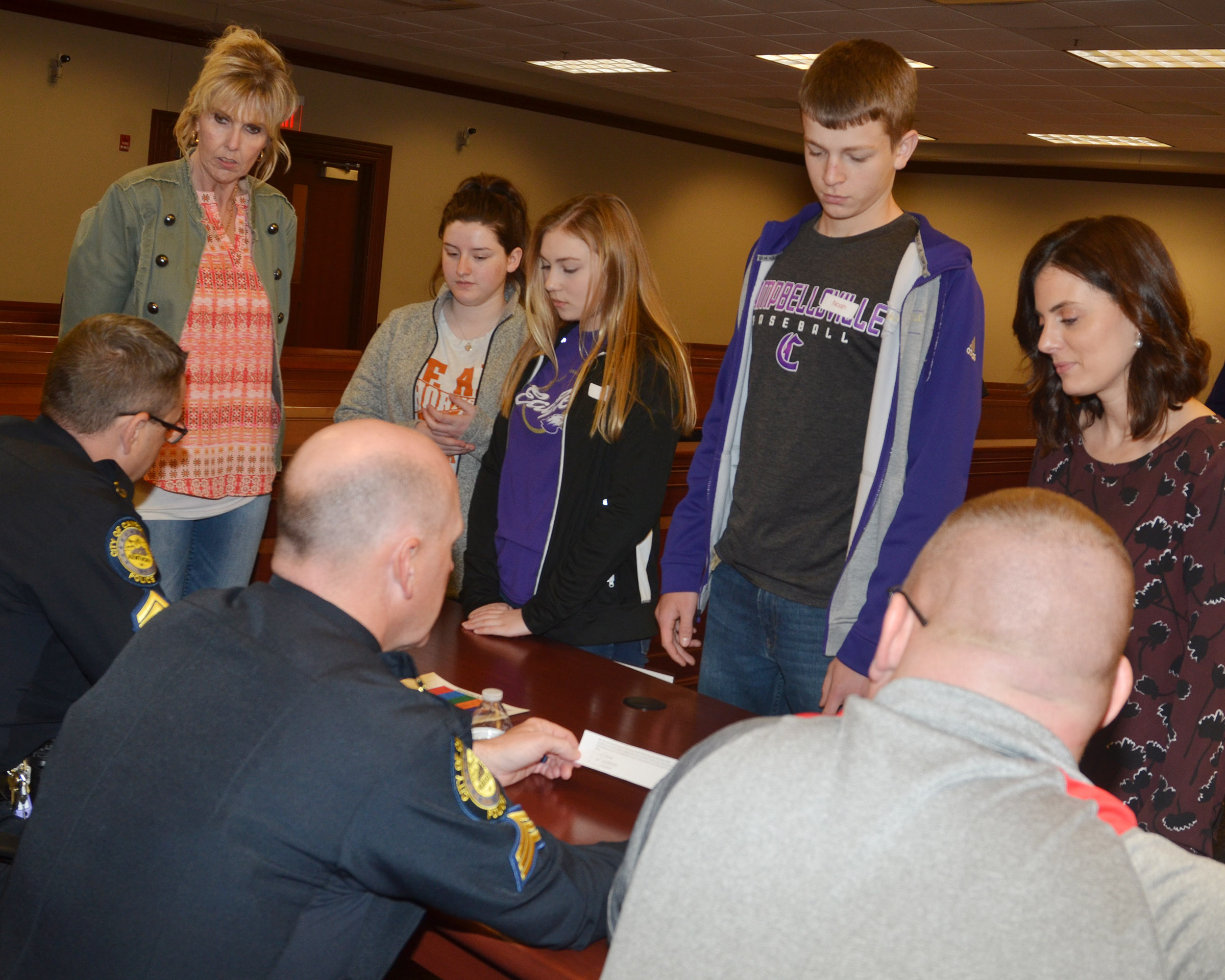 "CHS freshmen, center, from left, Alli Wilson, Bailey Smith and Noah Hughes and their ""parents"" talk with Campbellsville Police officers as part of the ""Truth or Consequences"" scenario."