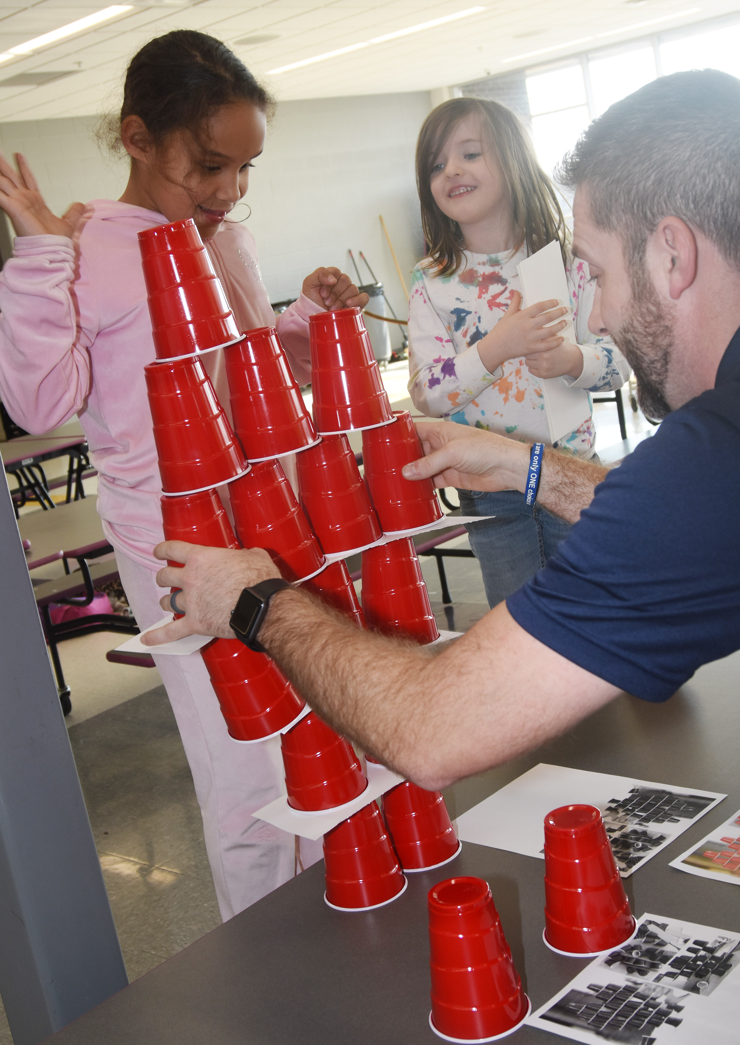 Campbellsville/Taylor County Chamber of Commerce Board member Chad Shively helps second-grader Amani Bridgewater, at left, and kindergartener Lasca Martin stack cups.