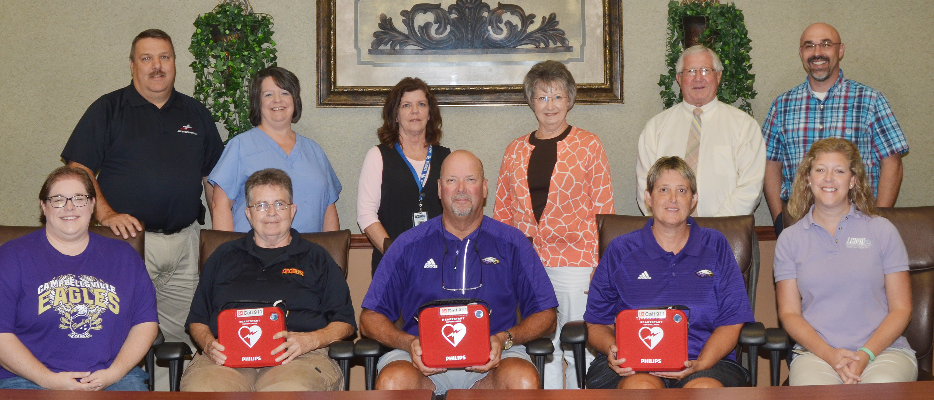 Campbellsville Independent Schools has received a grant from Taylor County Board of Health members to purchase three AED machines to be used at Campbellsville elementary, middle and high schools. The District partnered with Taylor County Health Department and Campbellsville/Taylor County EMS personnel to submit the grant proposal and make the purchase. From left, front, are Calen McKinney, public information officer/grant writer for Campbellsville Independent Schools; Denise Gupton, critical care paramedic/major at Campbellsville/Taylor County EMS; Tim Davis, Campbellsville High School athletic director; Katie Wilkerson, Campbellsville Middle School athletic director; and Jackie Hodges, health educator at Taylor County Health Department. Back, Dan Durham, Board of Health member and senior program director at Air Evac Lifeteam; Allison Griffiths, Taylor County Health Department office manager; Ruthie Bender, Taylor County Health Department nursing supervisor; Loretta Hash, Board of Health member and registered nurse representative for Taylor County; Eddie Rogers, Board of Health member and Taylor County judge/executive; and Shawn Crabtree, executive director at Lake Cumberland District Health Department.
