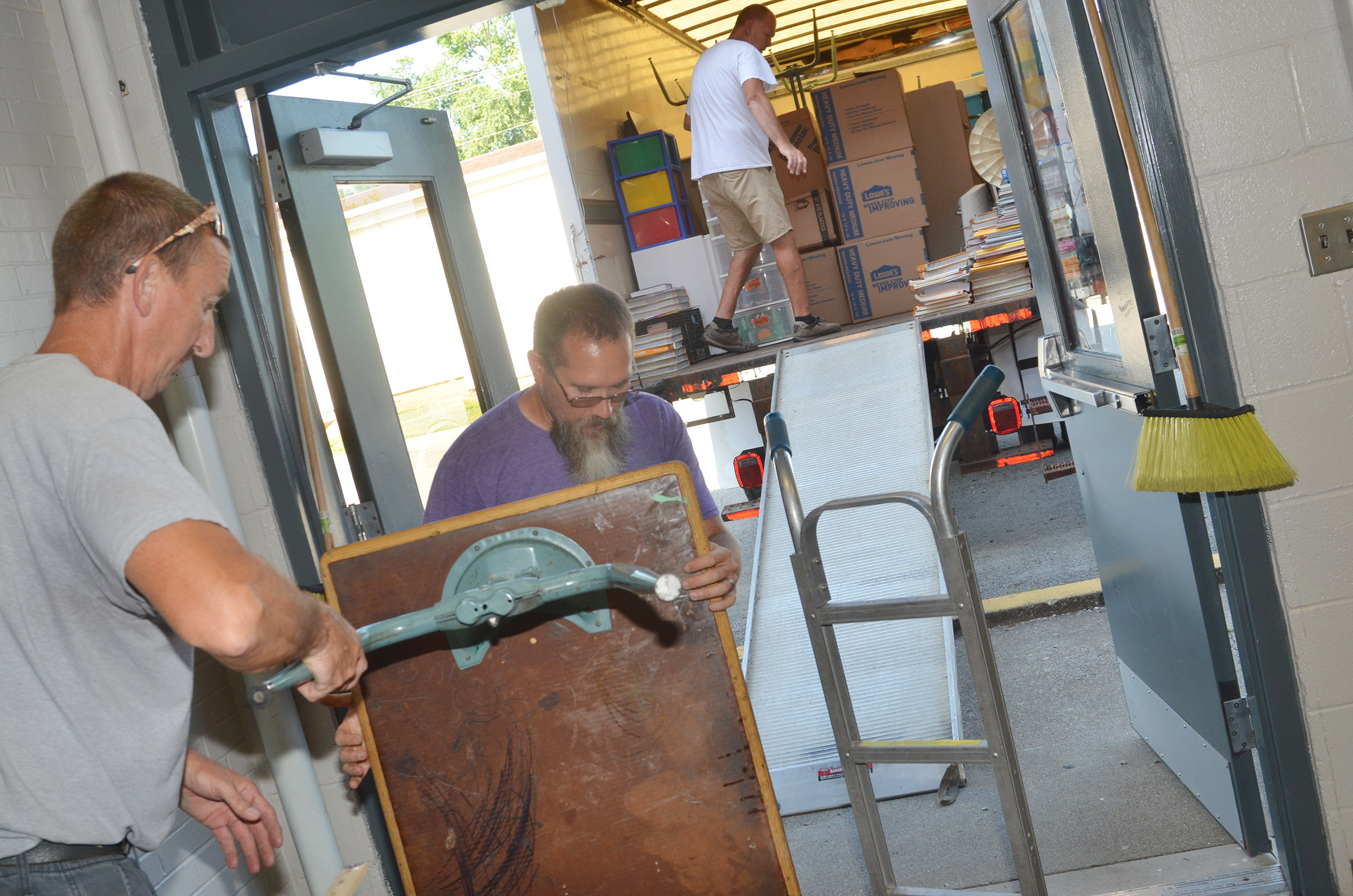 Carl Lee, at left, and Randy Bricken Jr., who work in maintenance, help teachers move their classrooms from the CMS campus to CES.