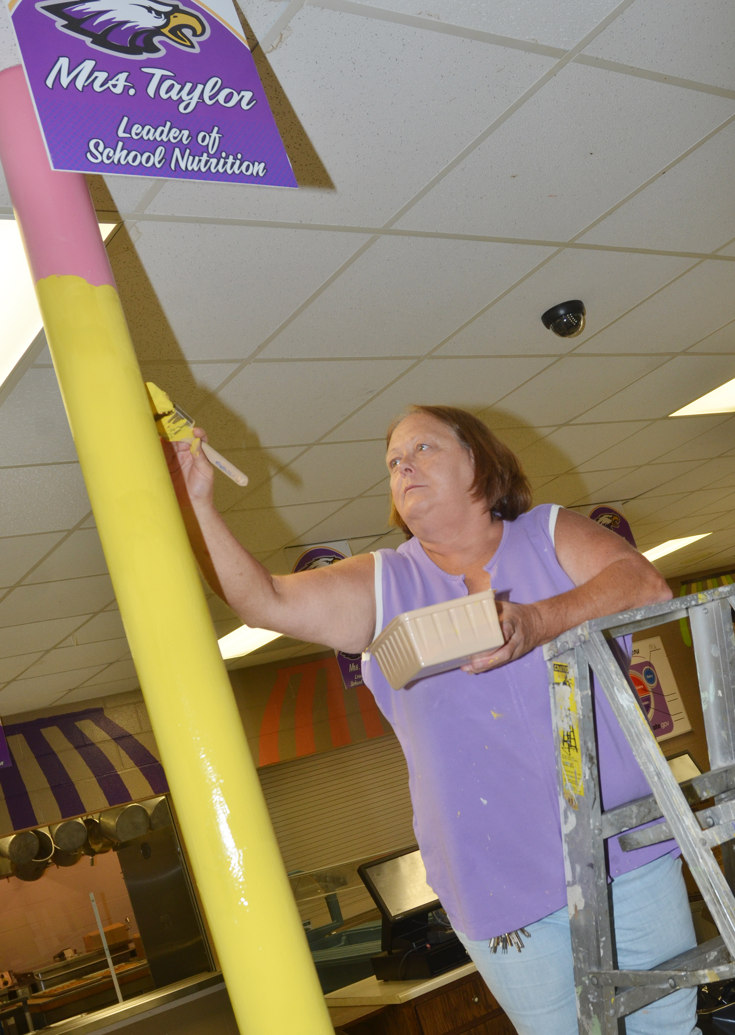 Cafeteria workers Darlene Burris paints the CMS/CHS cafeteria.