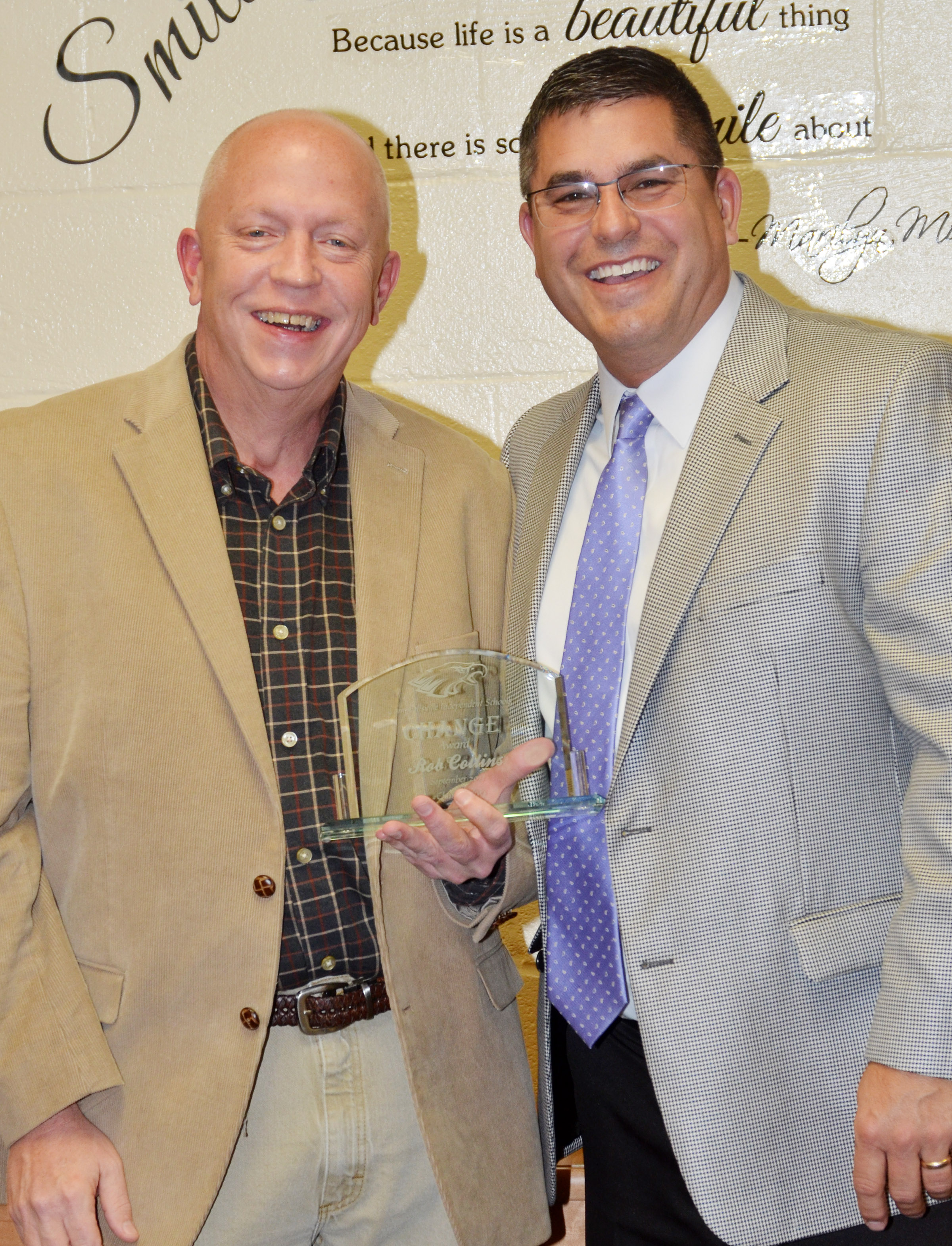 Campbellsville Independent SchoolsSuperintendent Kirby Smith, at right, honors Rob Collins, a radio personality at Q-104, with the community Change Award.