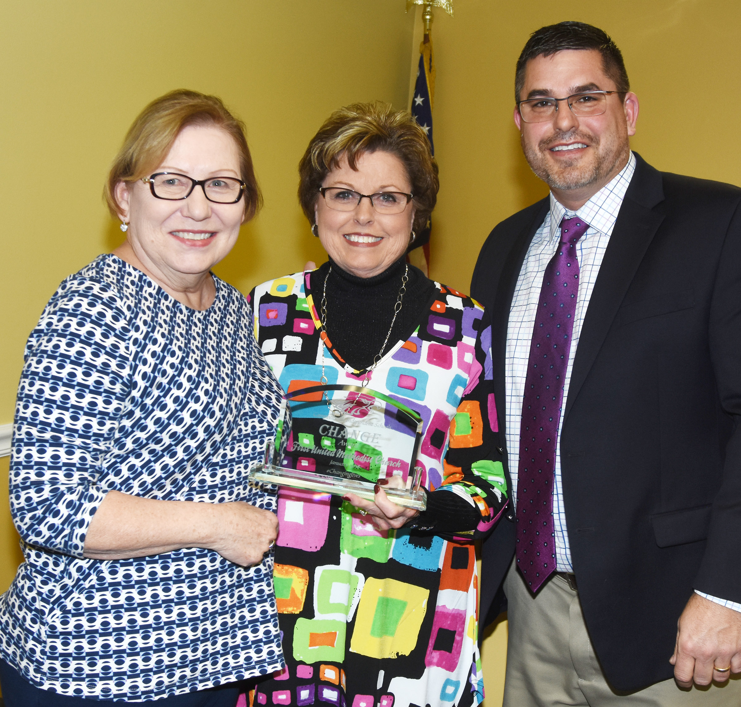 Campbellsville Independent Schools Superintendent Kirby Smith, at right, honors Linda Dernier, at left, and Lana Helm, who coordinate the Stars Child program at First United Methodist Church, with the community Change Award.
