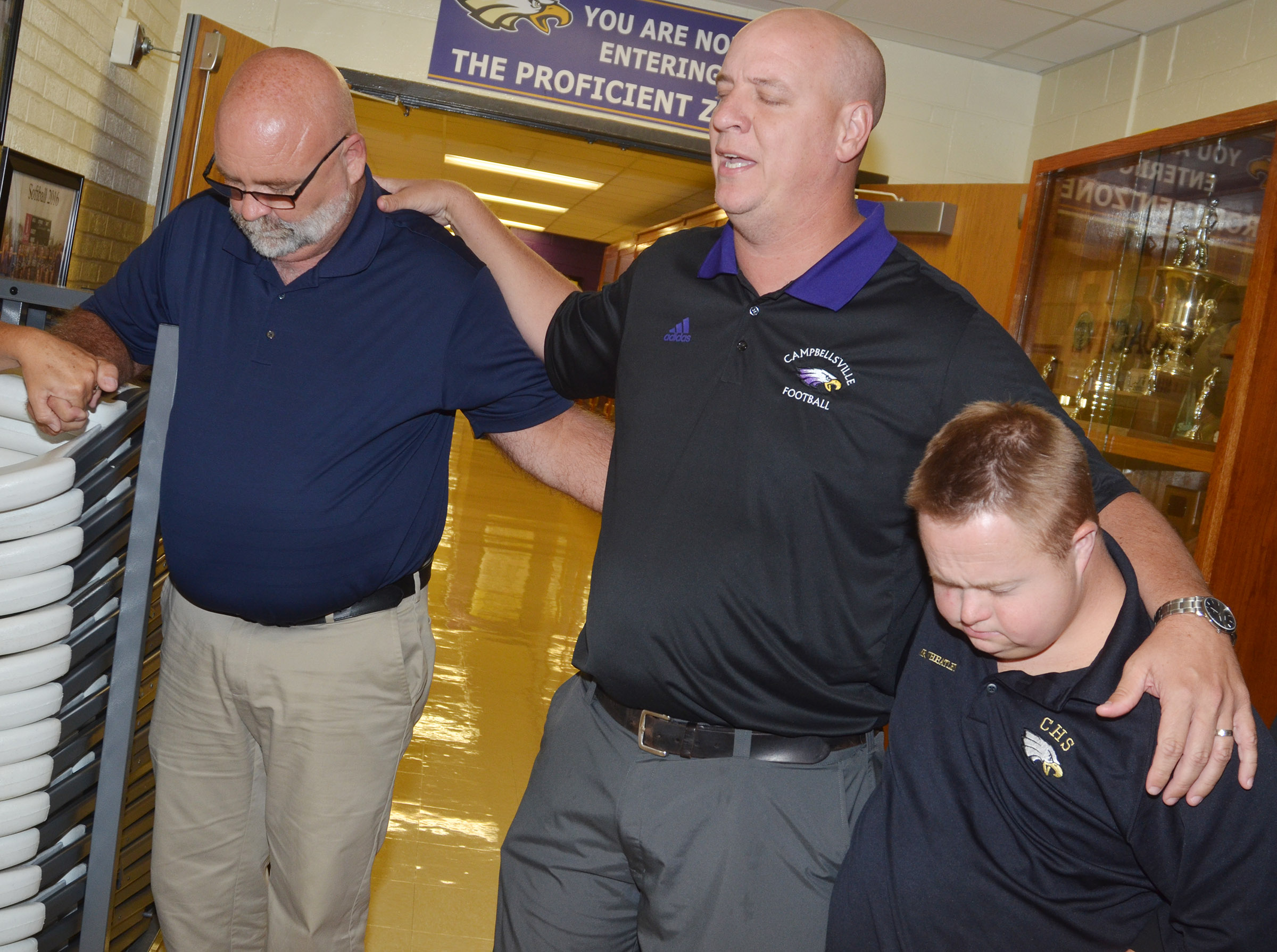 CHS Principal David Petett, center, prays for his students.