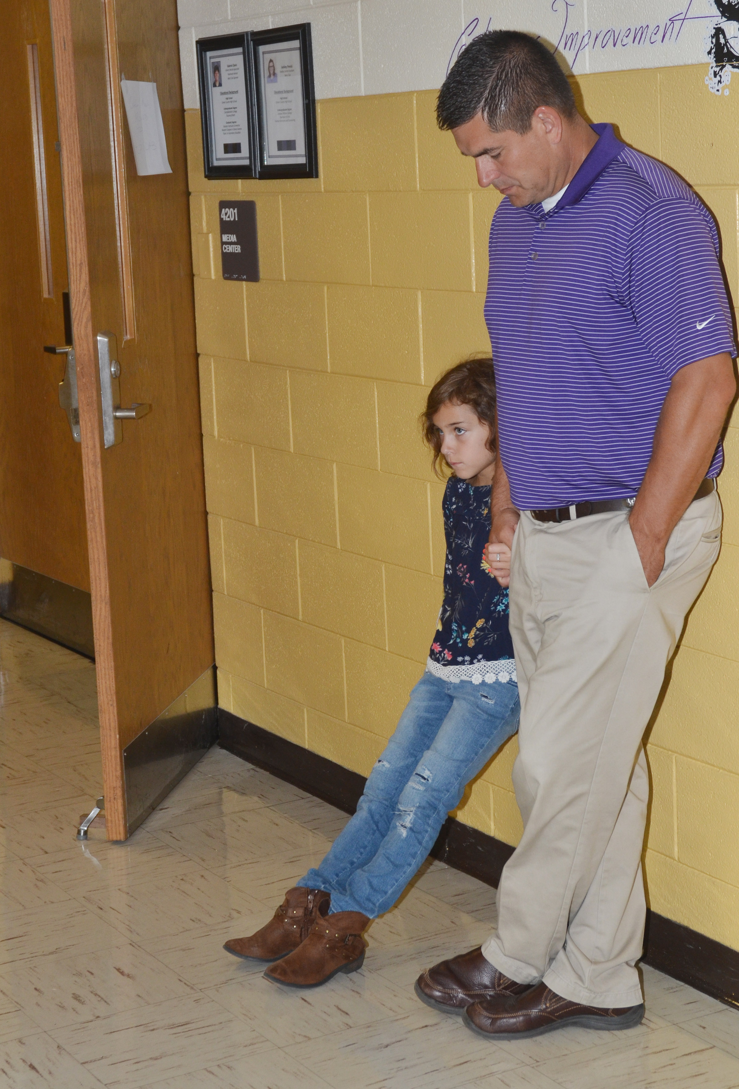 CIS Superintendent Kirby Smith and his daughter Karsyn pray in the CHS hallway.
