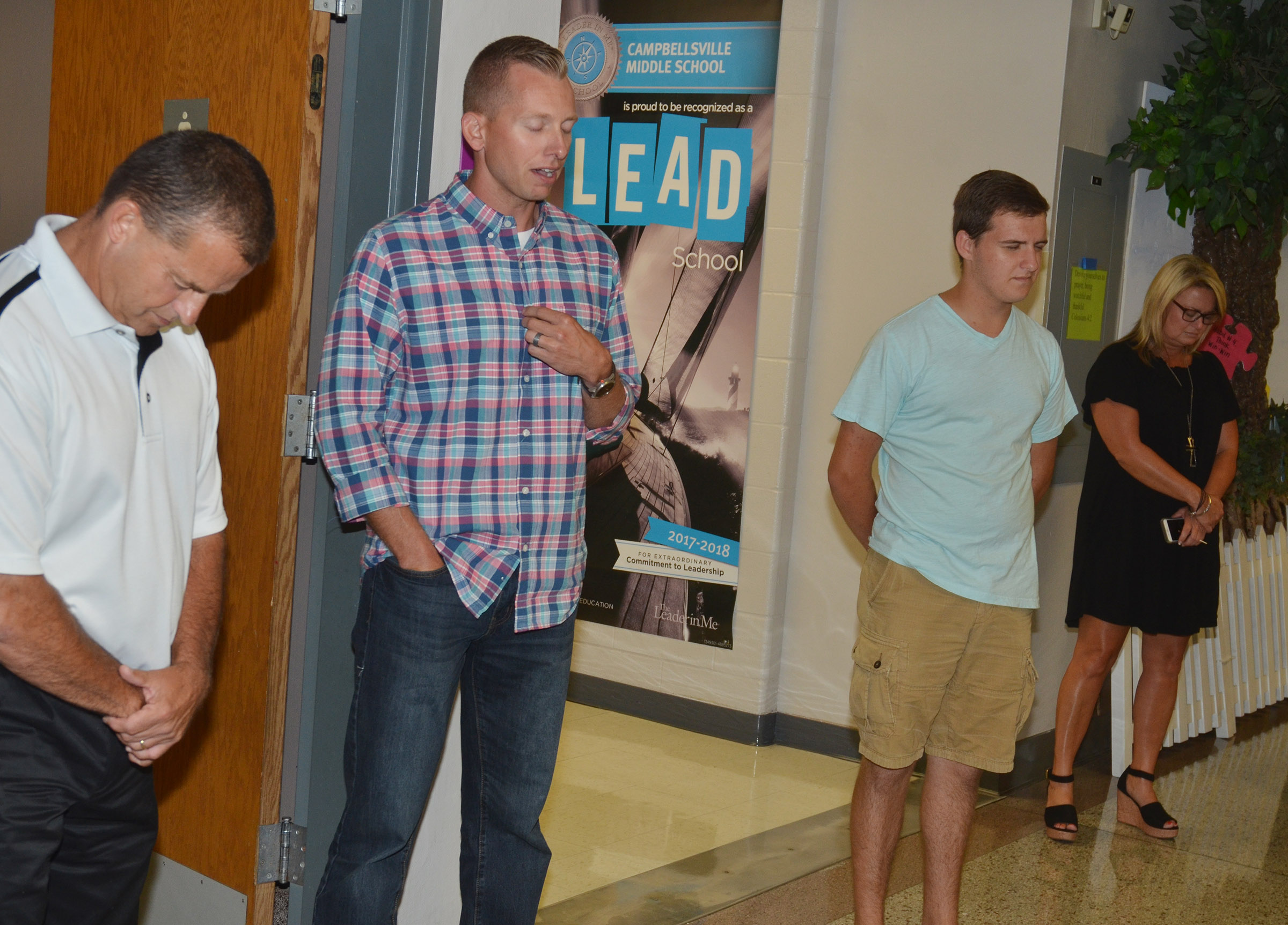 CMS Principal Zach Lewis, second from left, prays for his school.