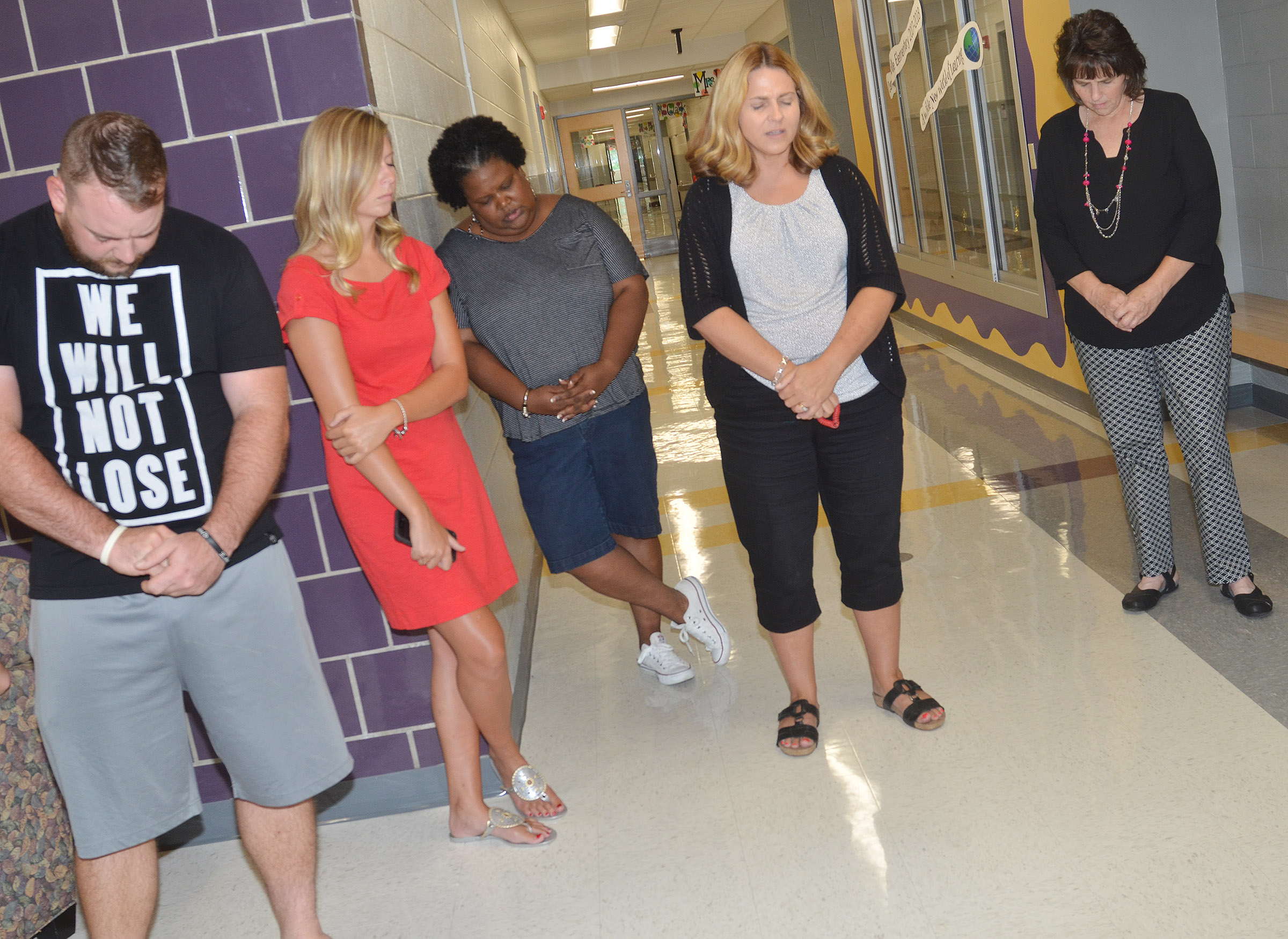 CES Guidance Counselor Sonya Orberson, second from right, prays for her school.