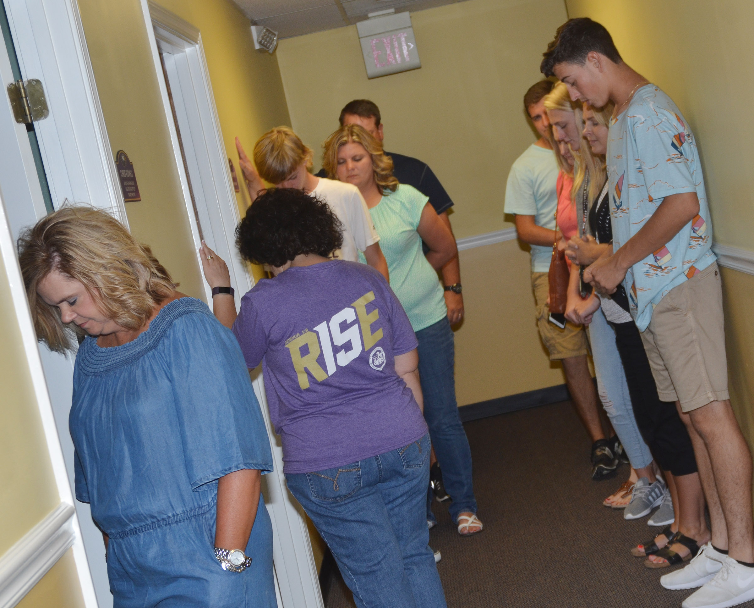CIS staff members, students and parents pray at the Campbellsville Board of Education office for the new school year.