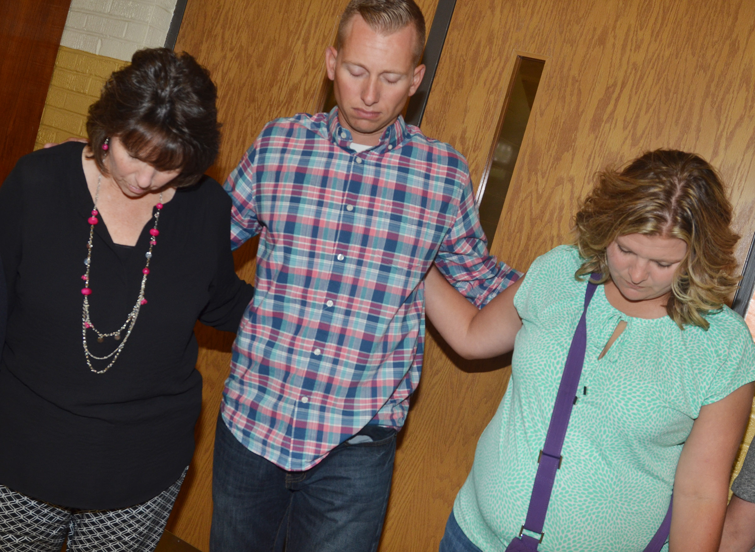 From left, CHS teacher Deanna Campbell, CMS Principal Zach Lewis and CES teacher Tammy Hash pray together.