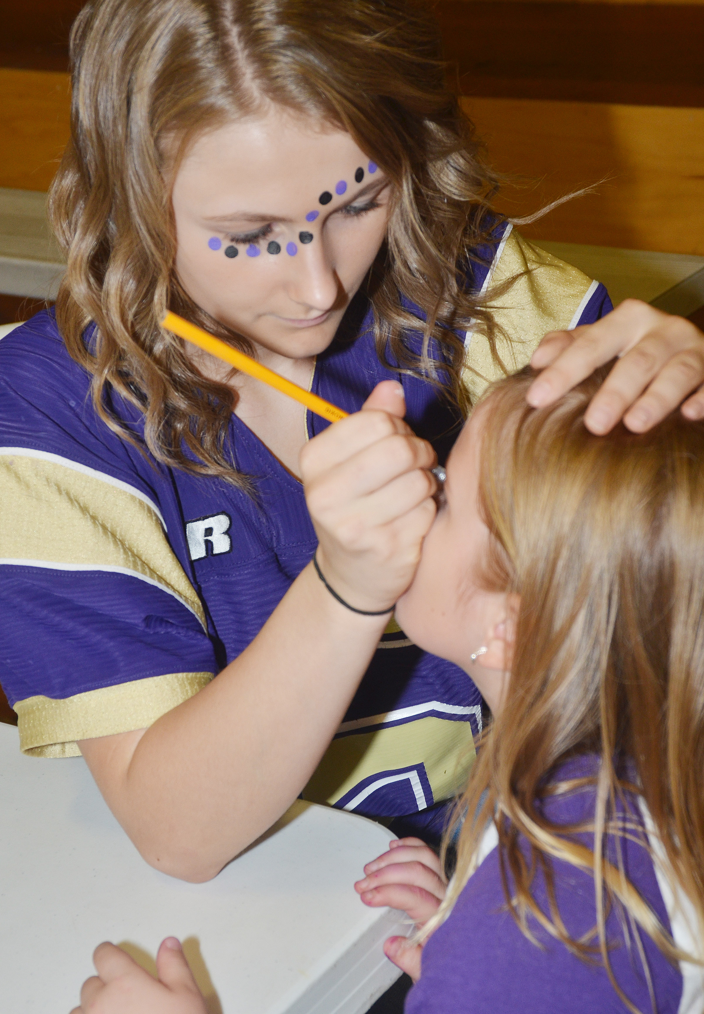CHS sophomore Victoria Cox paints CES first-grader Aubreigh Knifley's face.