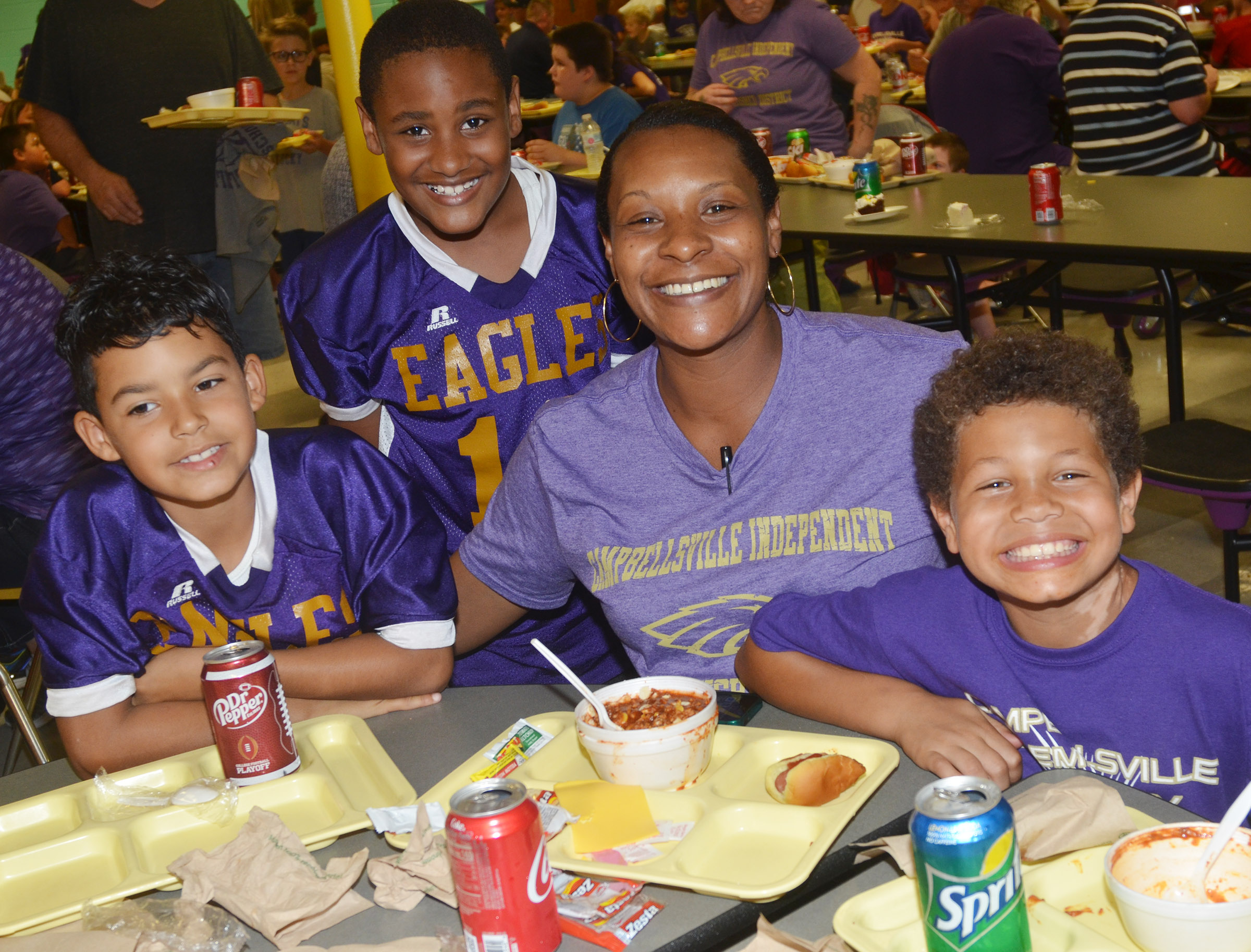 From left, CES second-grader Rizzo McKenzie and his brother fourth-grader Shaiden Calhoun pose for a photo with their mother, Chanda Calhoun, and their cousin Tristen Williams, a second-grader, as they eat chili.