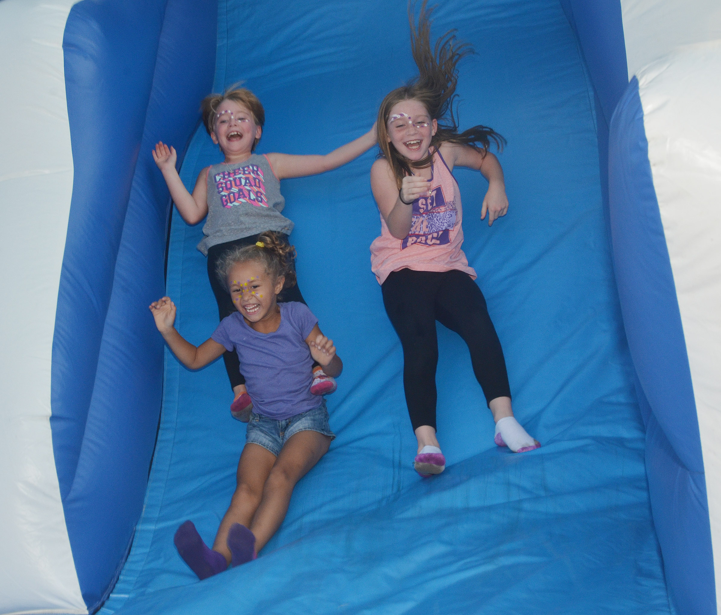 From left, CES kindergartener Fallyn Smith and second-graders Maddie Brunelle and Izzy Brunelle slide.