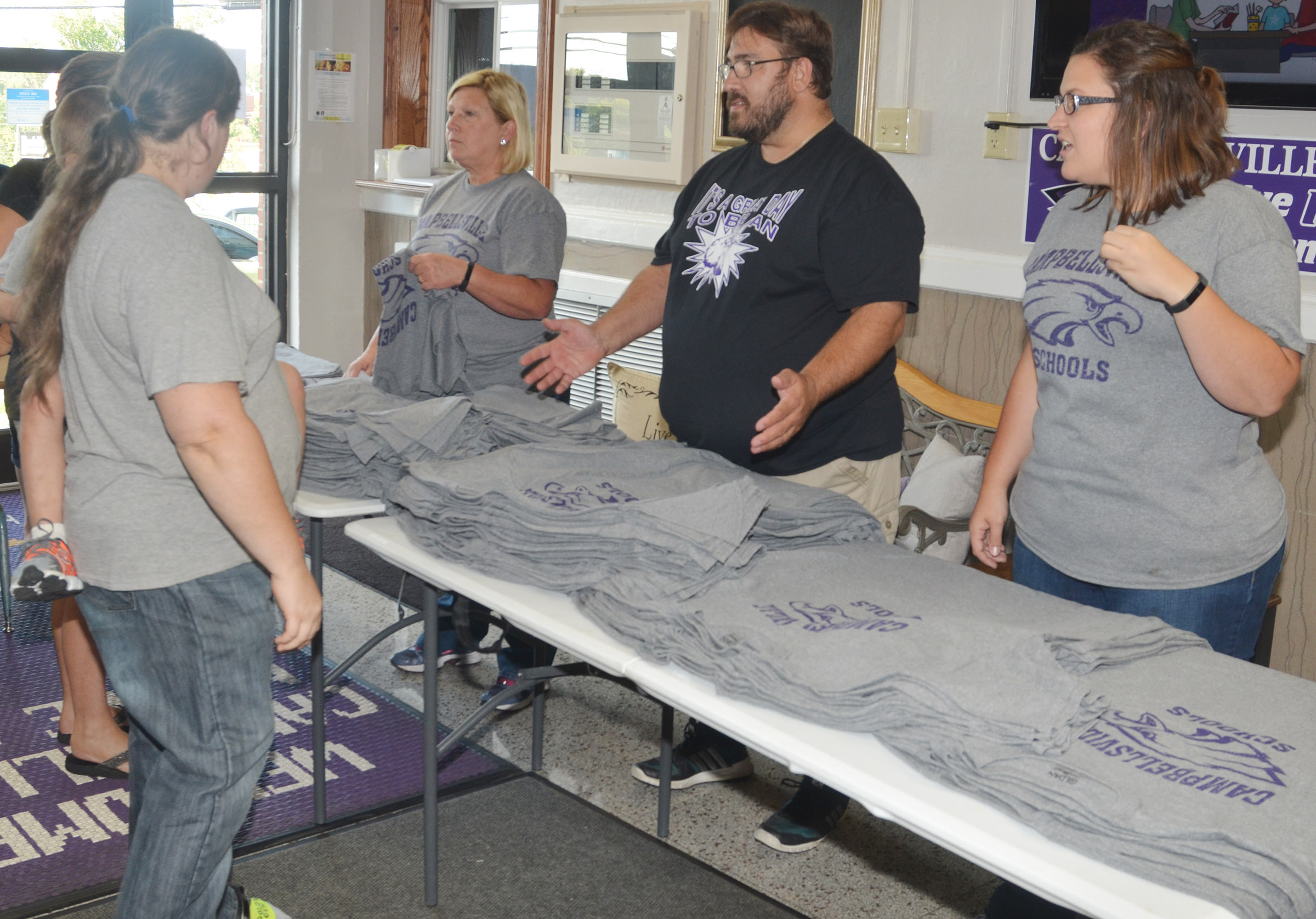 From left, CMS teacher Jan Speer, parent Mark Wiedewitsch and teacher Robbilyn Speer pass out Eagle t-shirts.