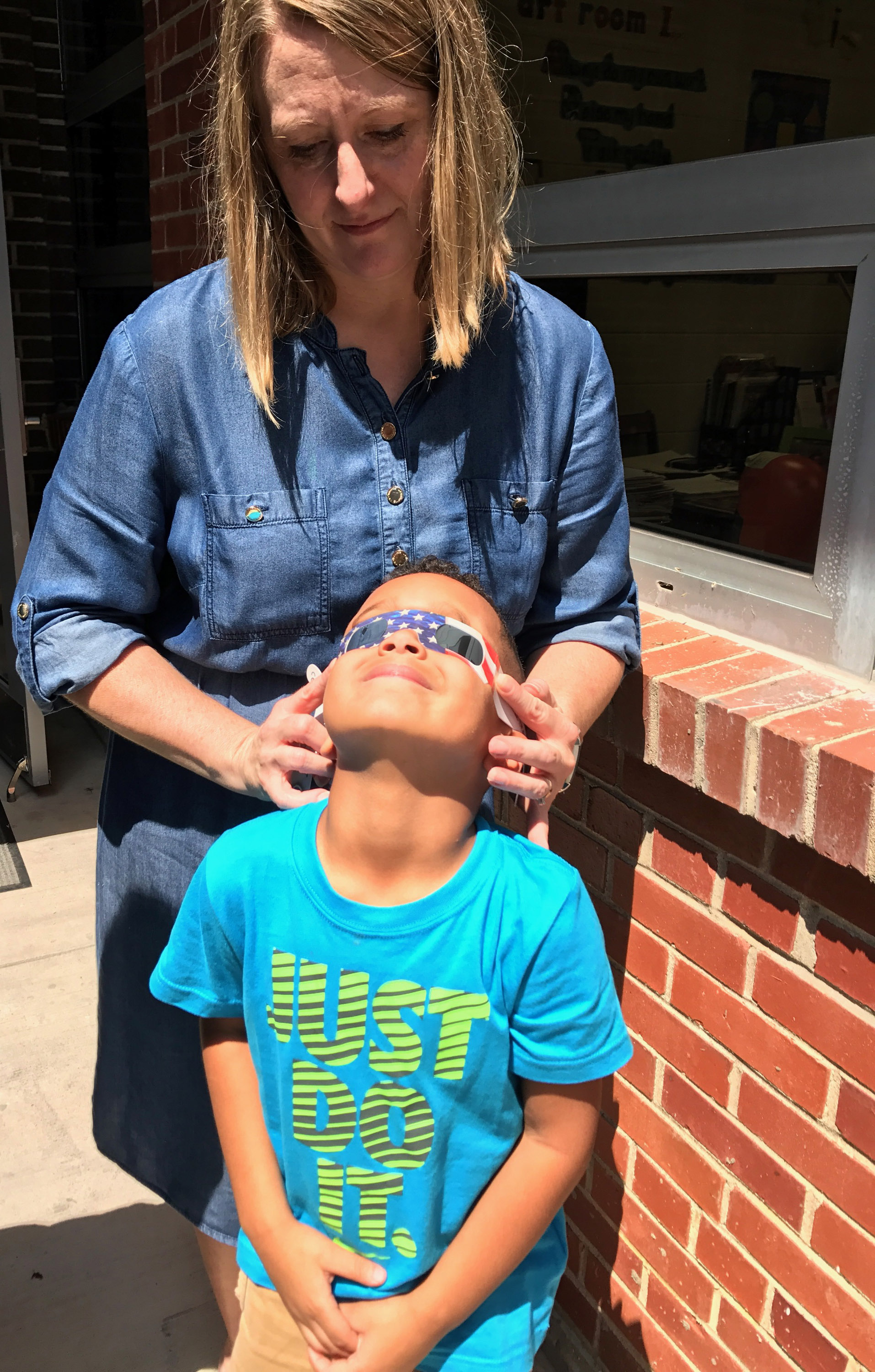 CES teacher Laura Dicken puts solar glasses on kindergartener Kingston Cowherd.