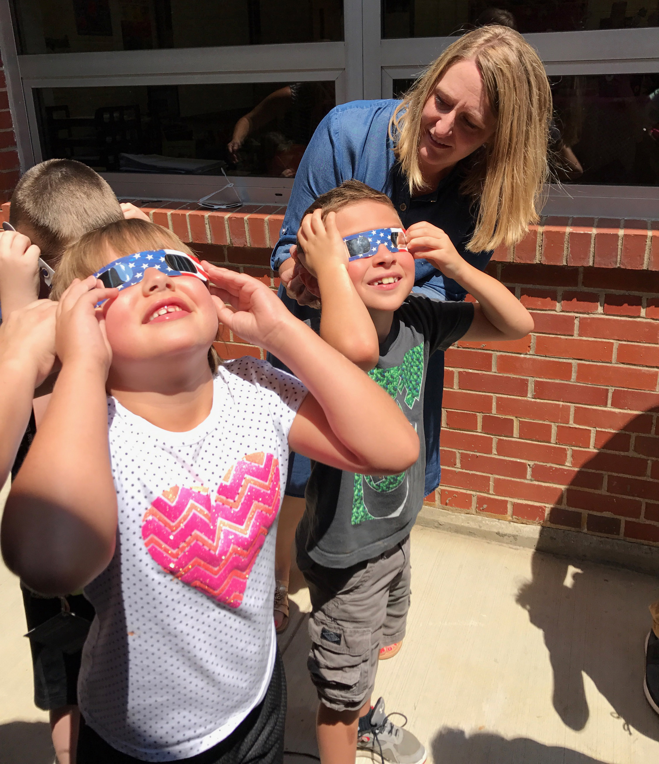 CES teacher Laura Dicken makes sure second-graders Addysen England, at left, and Bryson Gabehart are wearing their solar glasses.