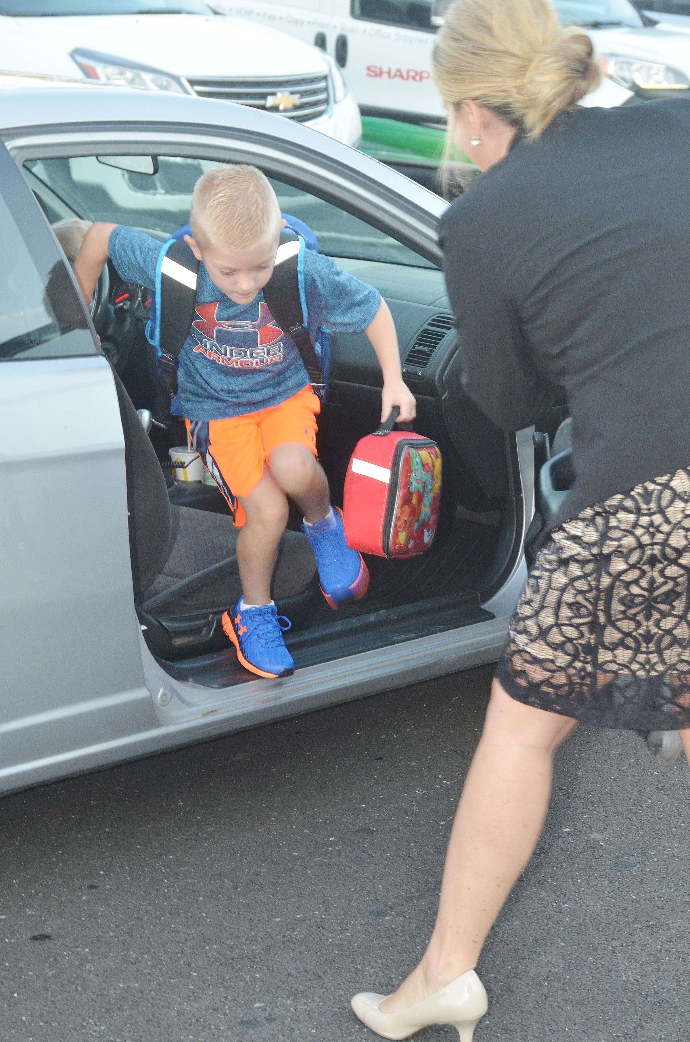 CES Principal Elisha Rhodes helps third-grader Evan Cundiff out of the car for his first day of school.