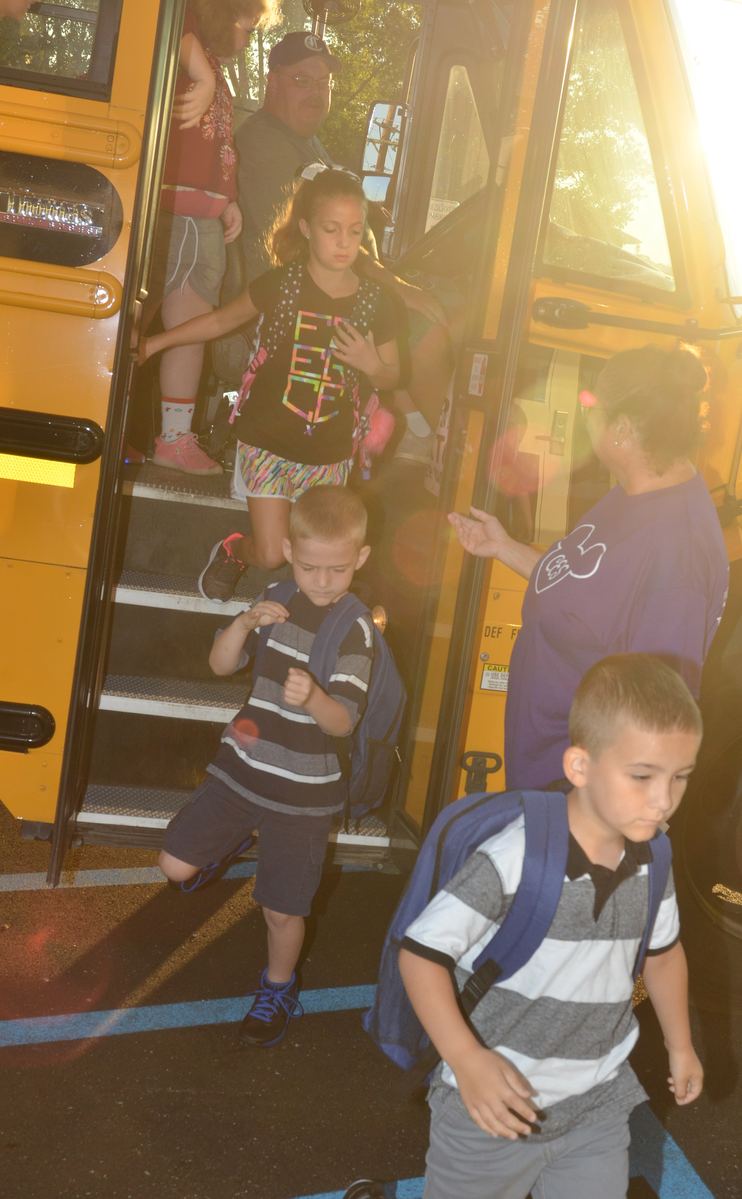 CES media center assistant Lois Kemp helps students off the school bus.
