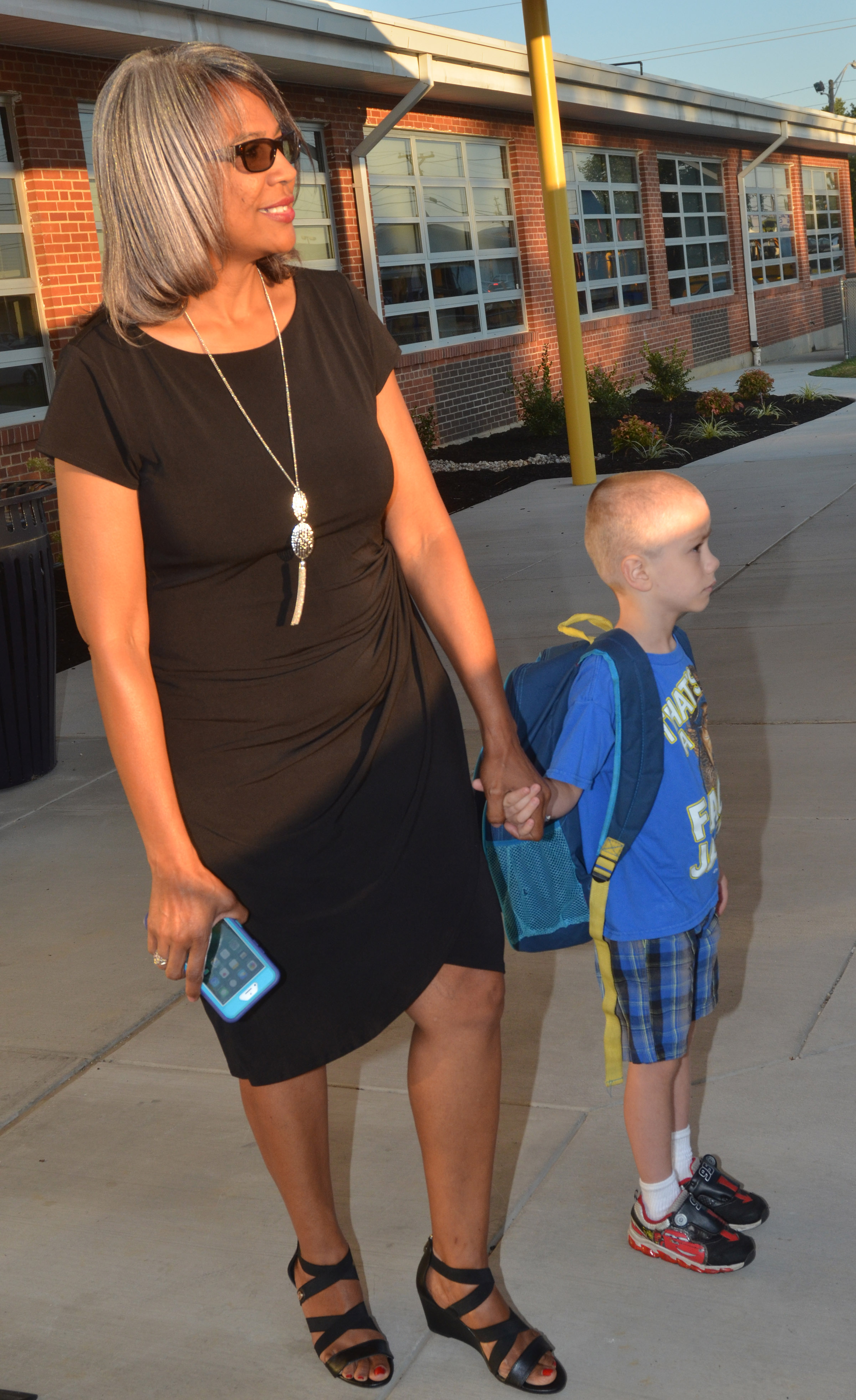 CES Assistant Principal Doretha Sanders walks first-grader Alex Eggers into school.