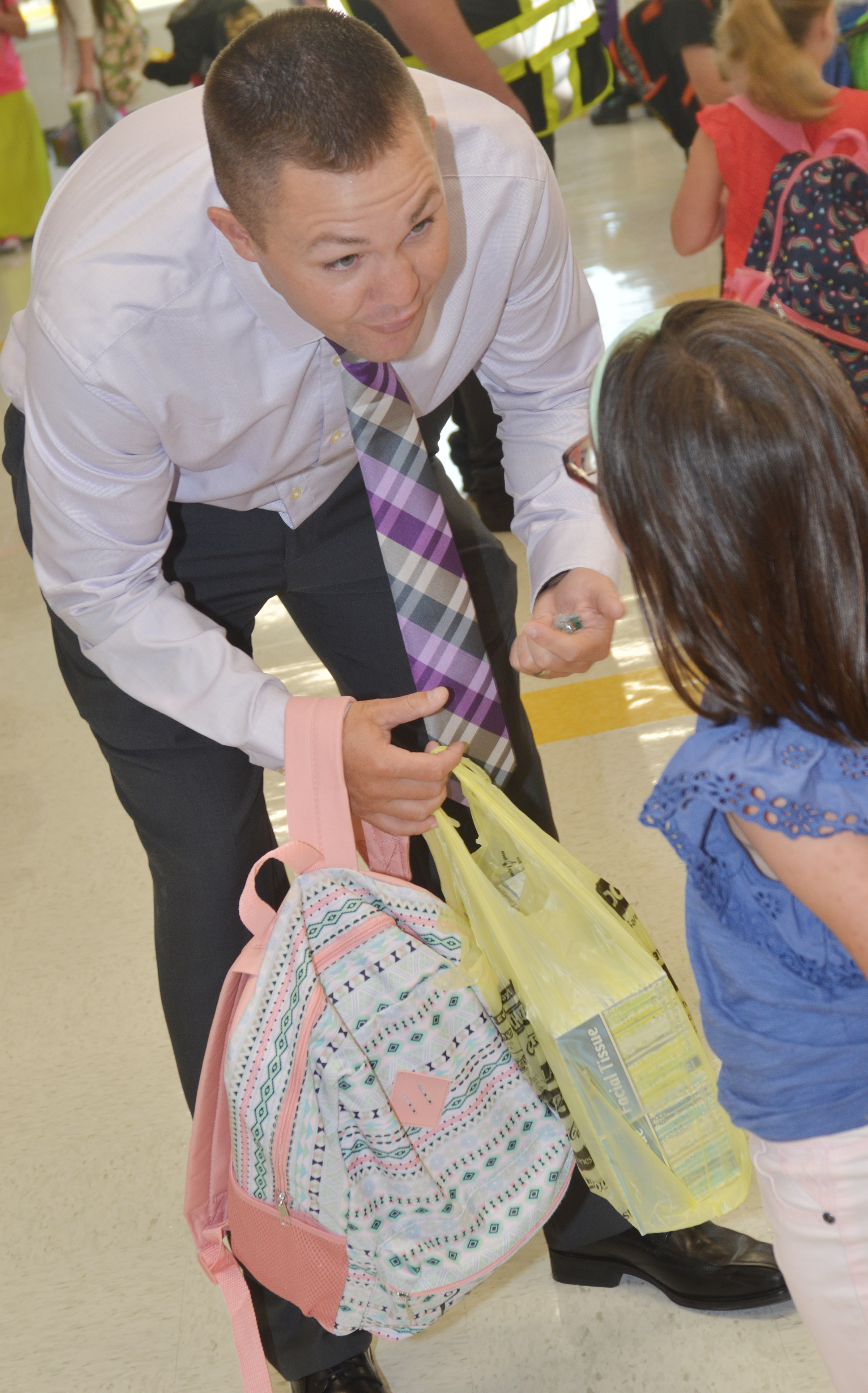 CES Assistant Principal Weston Jones helps first-grader Trinity Clark carry her school supplies.