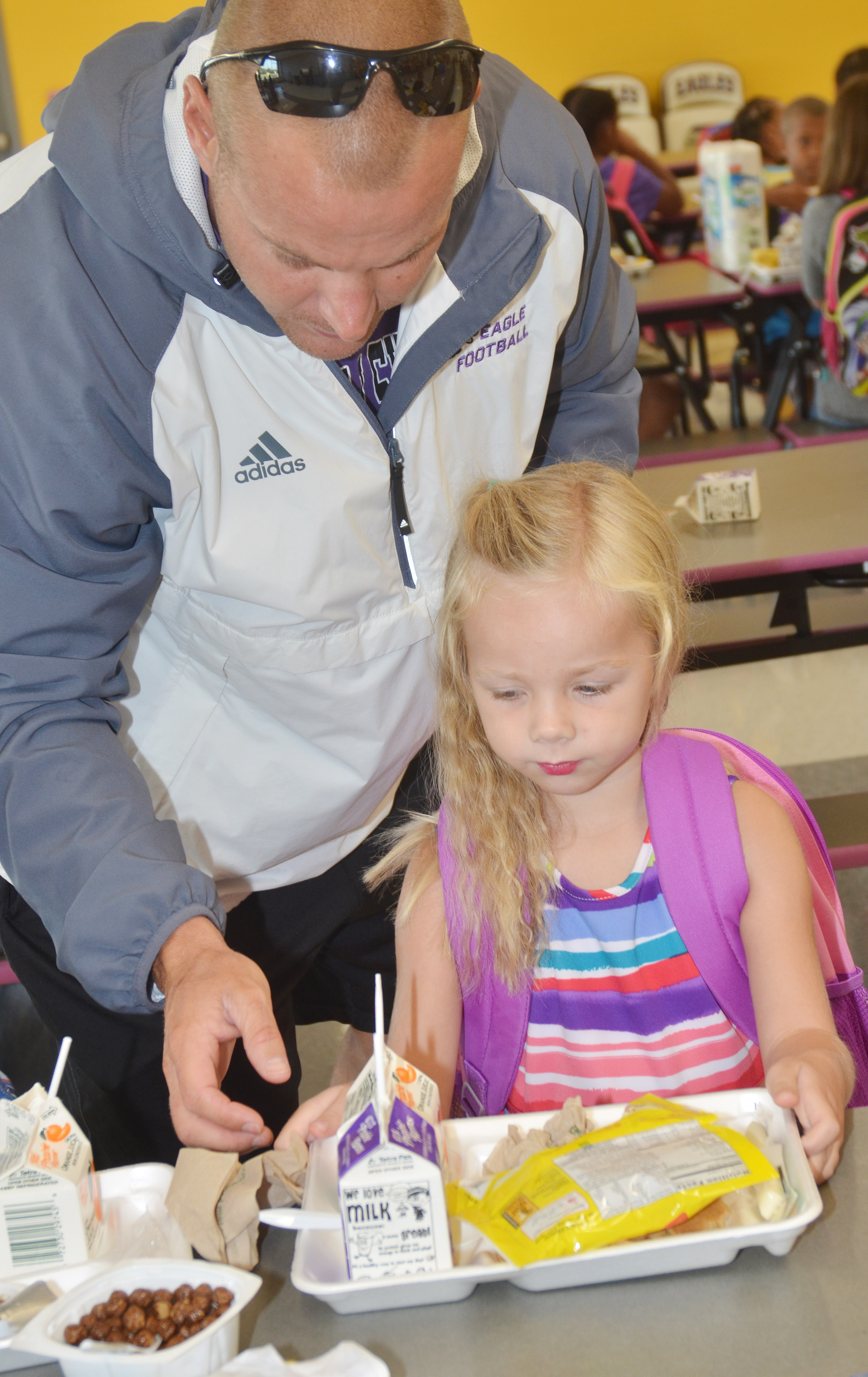 CES kindergartener Trinidy Gribbins gets some help with her breakfast from her dad Robbie.