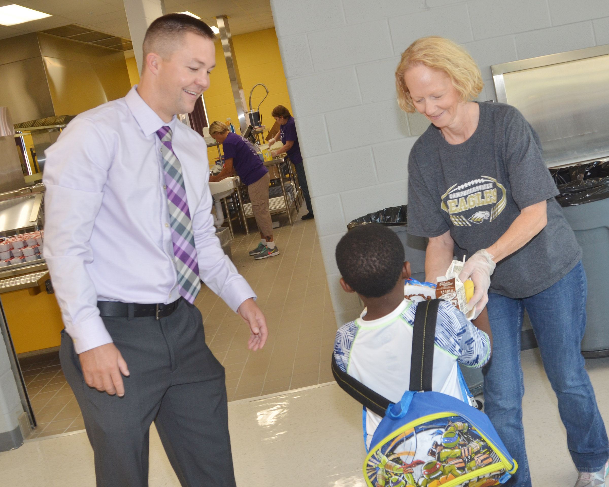 CES Assistant Principal Weston Jones and CIS Food Service Manager Lois Lacy help kindergartener LaTayvion Brown throw away his breakfast tray.