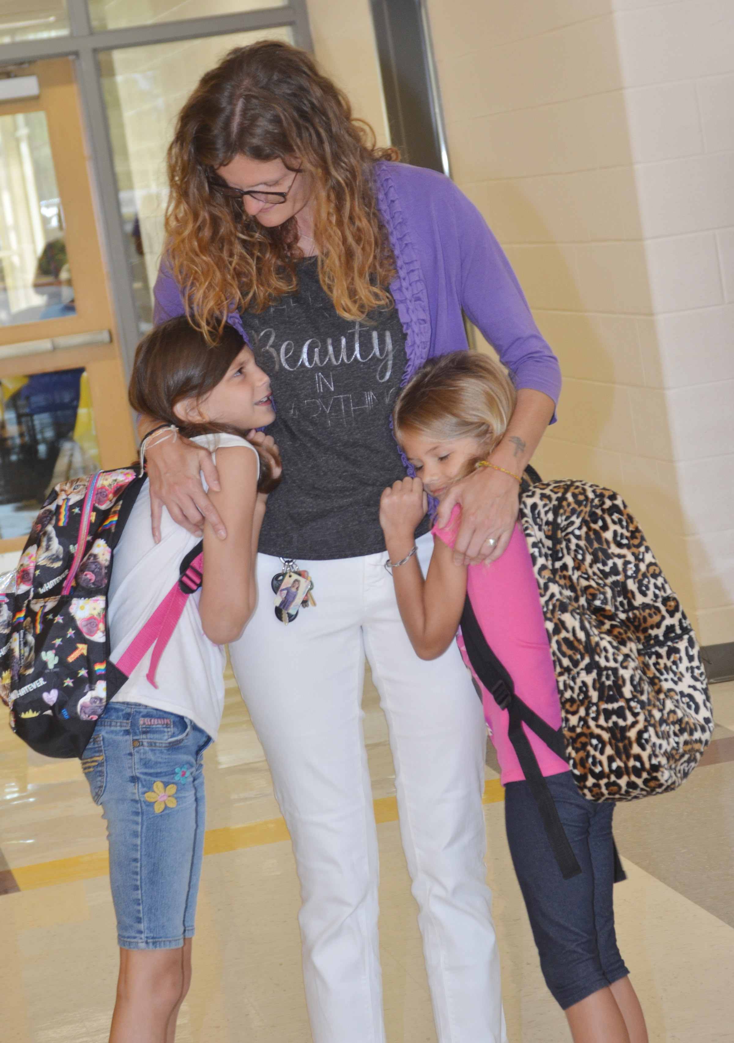 CES fourth-grader Madie Gebler, at left, and first-grader Gracie Gebler hug their mother, Rebekah Taylor, as they start their first day of school.