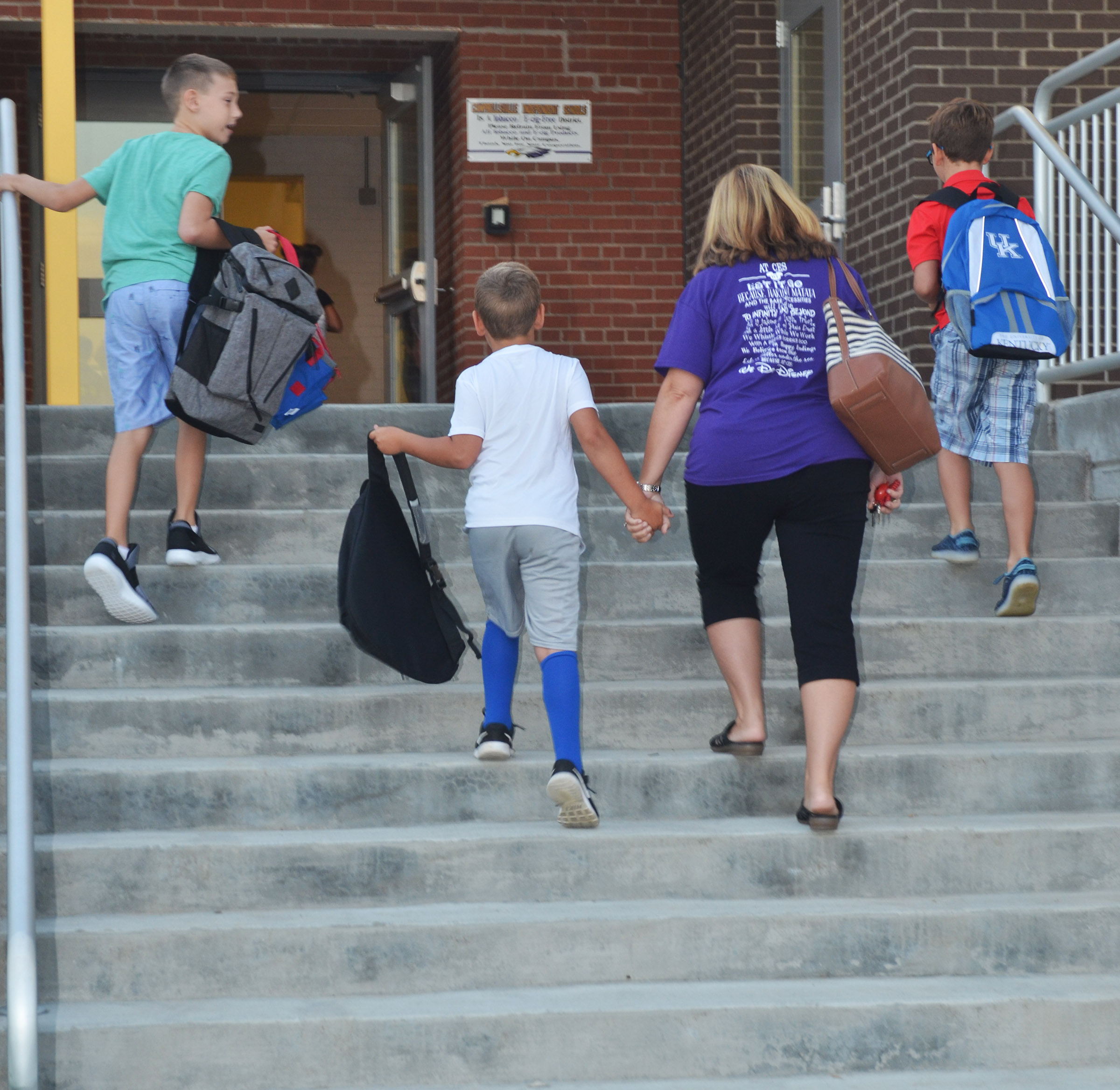 CES Guidance Counselor Sonya Orberson walks into school with, from left, third-grader Aidan Wilson, first-grader Braxton Rhodes and third-grader Tye Rhodes.
