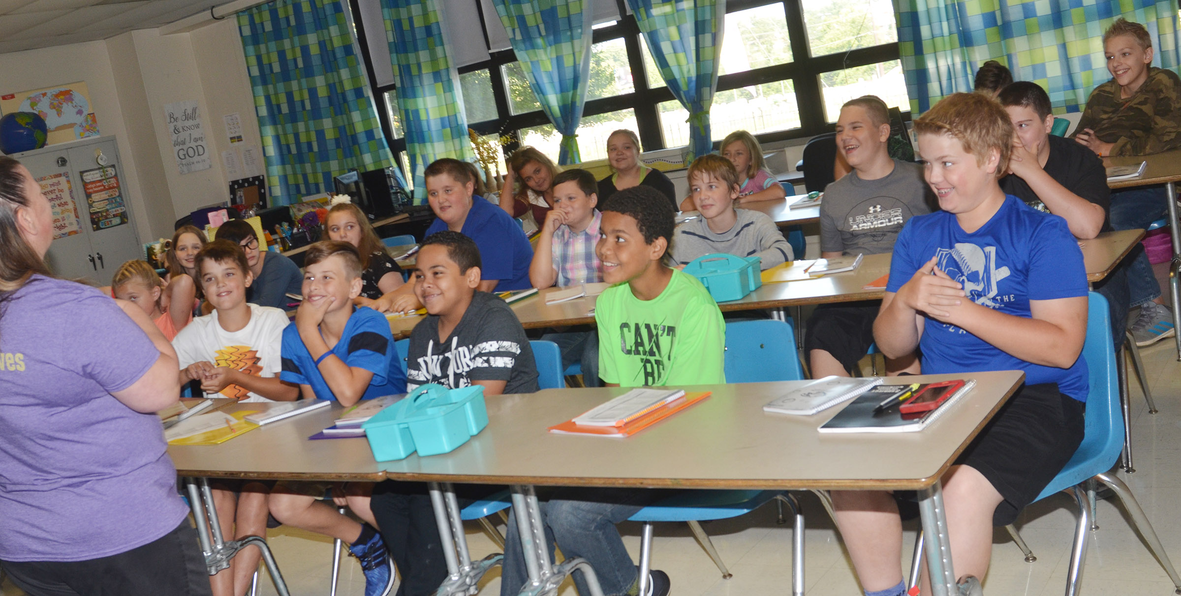 CMS sixth-graders smile as they listen in their classroom.