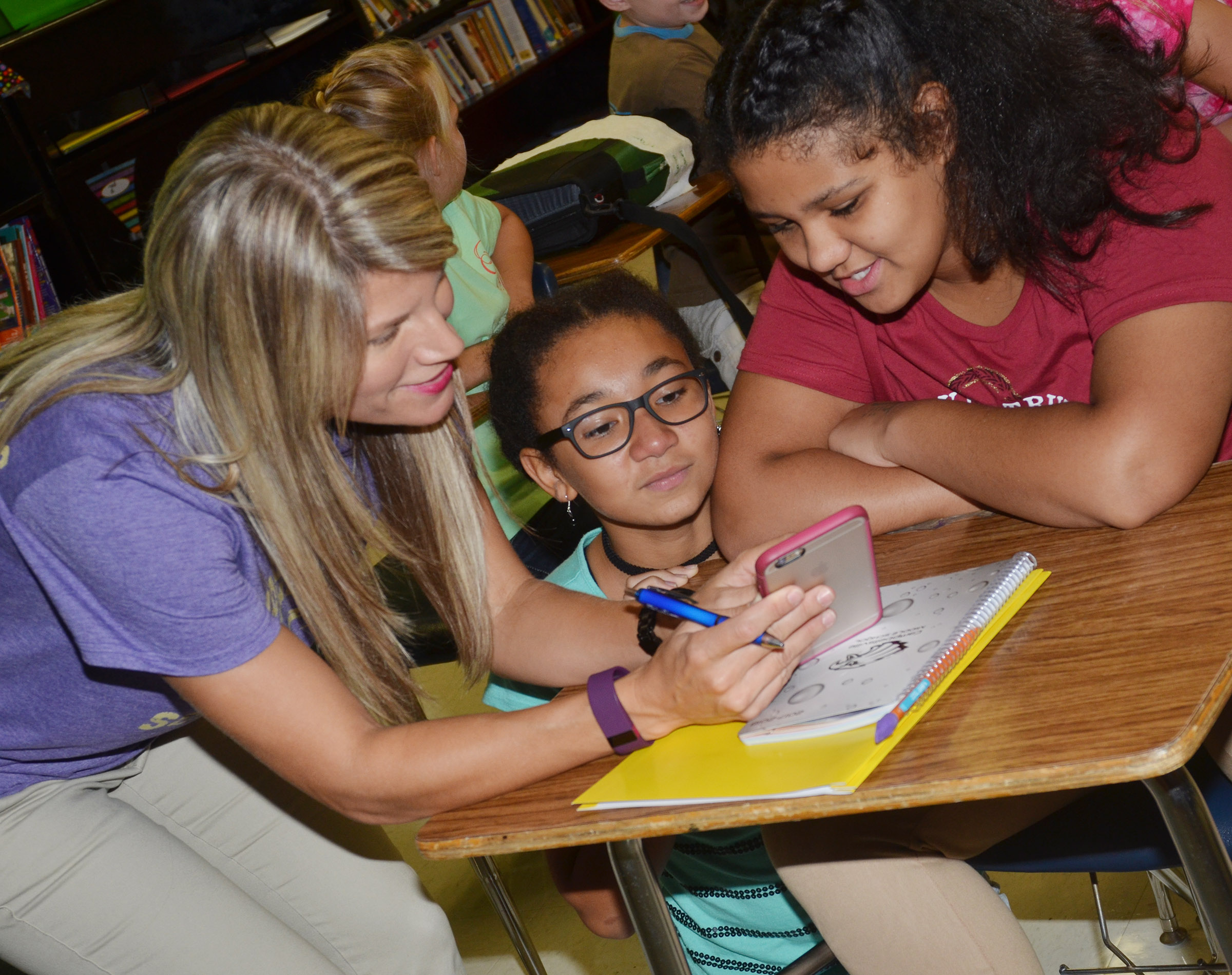CMS sixth-grade teacher Andrea Gribbins looks at photos with students Keely Thompson, at left, and Kehleigh Vaught.