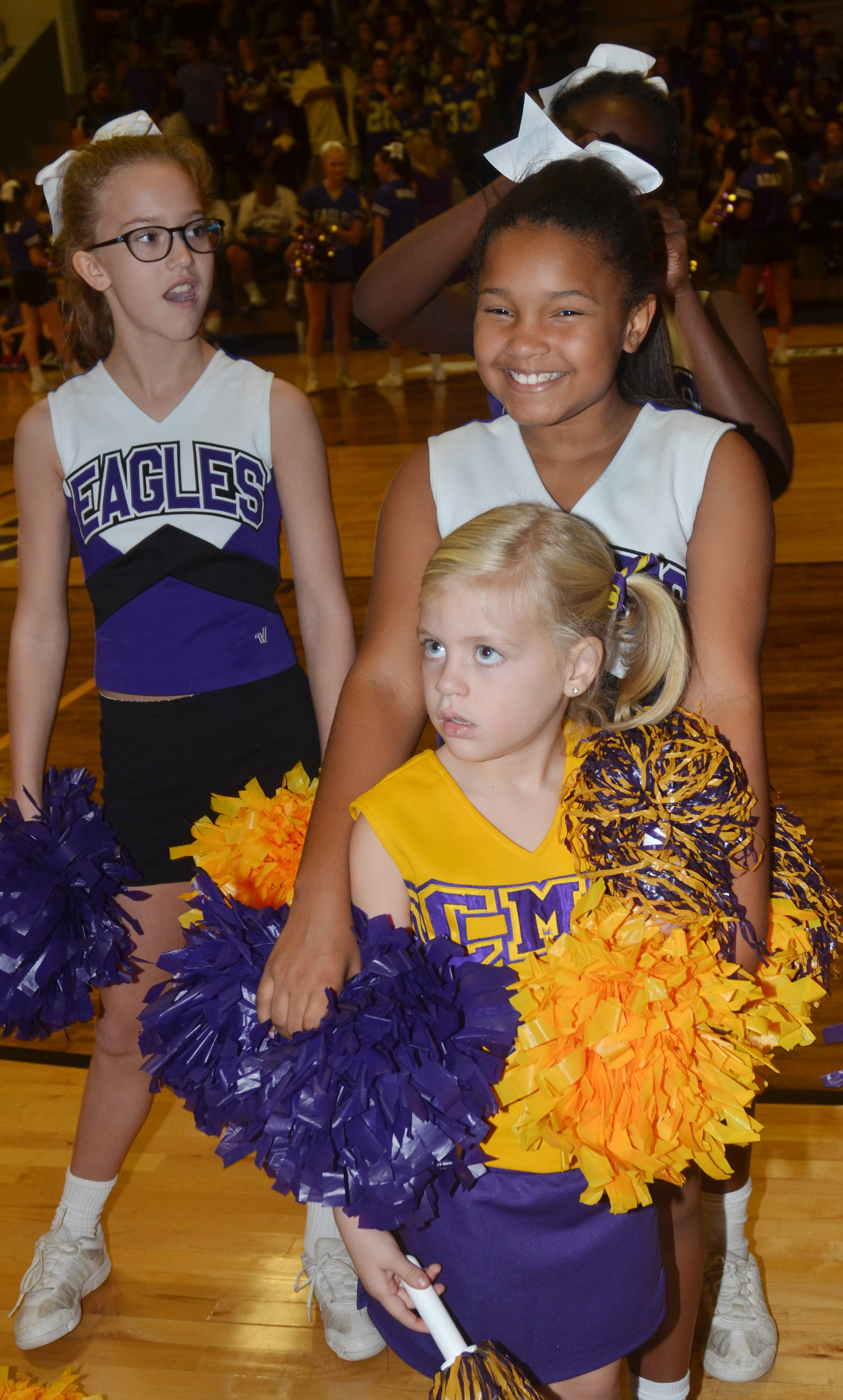 CMS sixth-grader Chloe Thompson, at left, and CES fifth-grader Jaclyn Jackson cheer for the Eagles, with help from CES kindergartener Remi Petett.