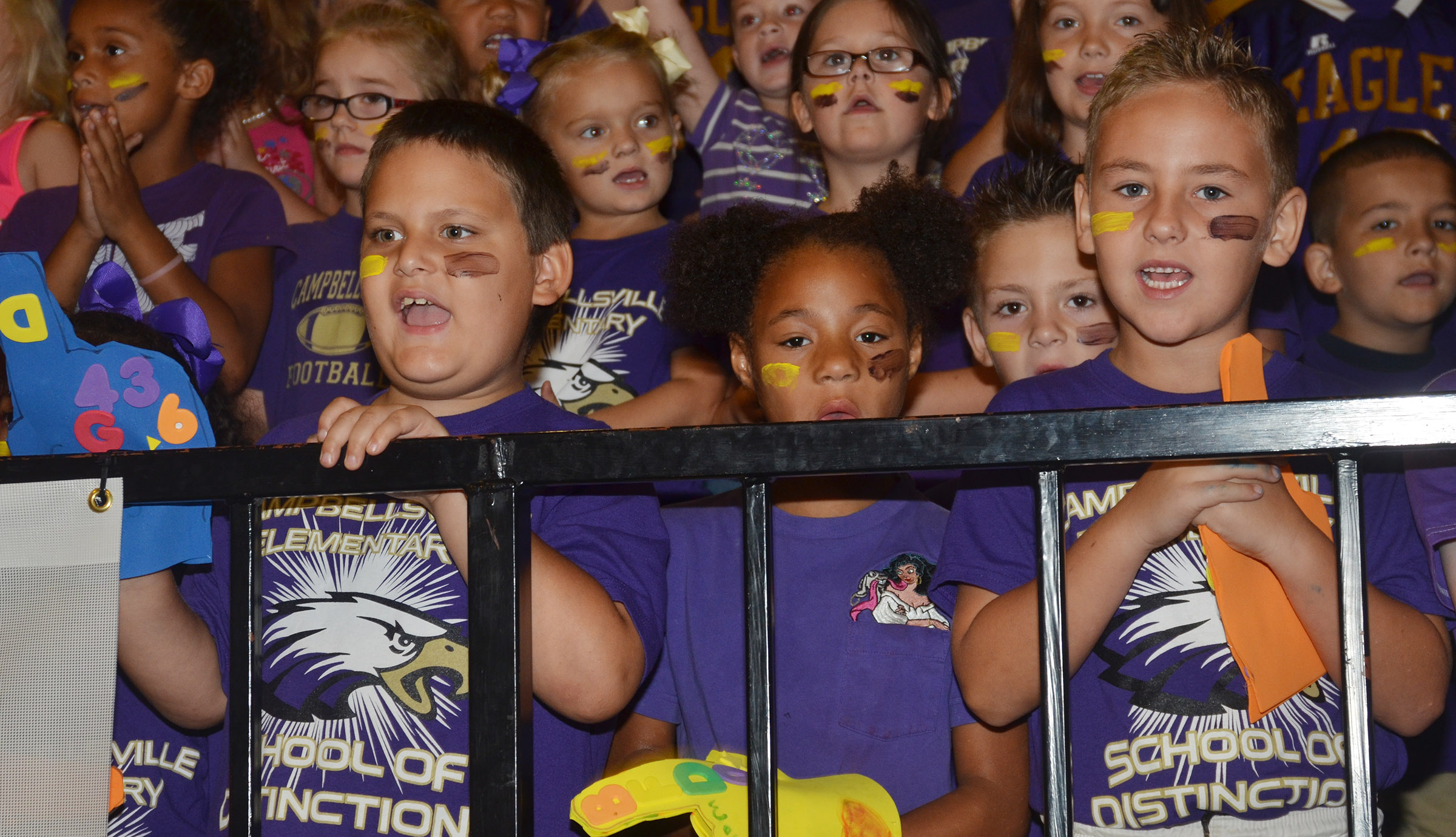 From left, CES first-graders Cloud Malone, Brea Miller and Braxton Rhodes cheer.