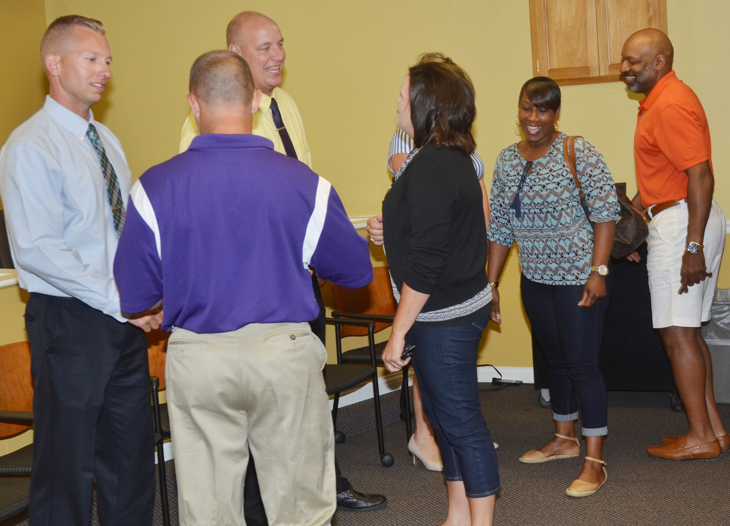 From left, CMS Principal Zach Lewis, CHS Principal David Petett and CES Principal Elisha Rhodes, hidden, greet teachers, staff members and parents.