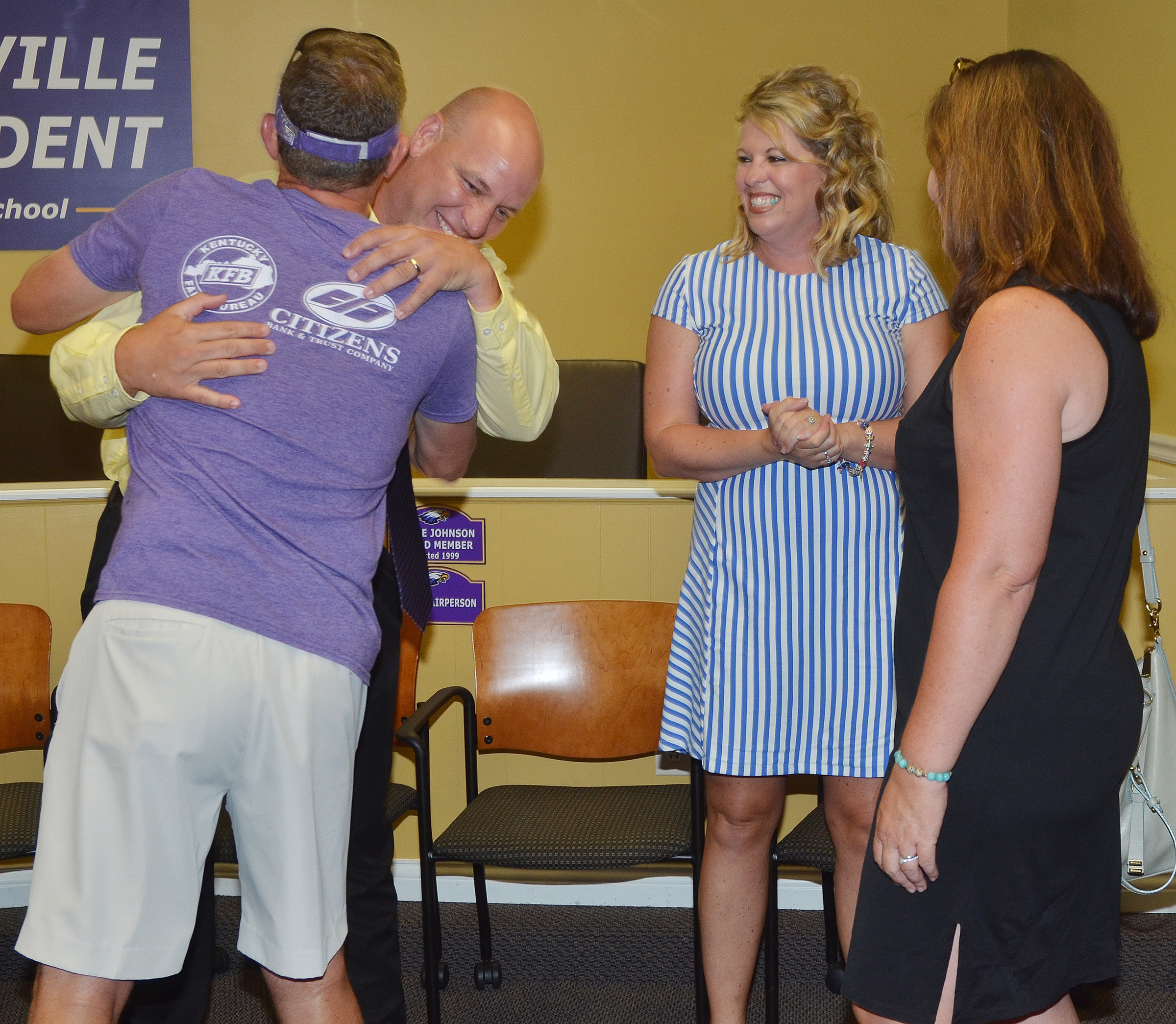 CHS Principal David Petett gets a hug from Herb Wiseman, who is a virtual learning teacher at CHS. At right, CHS teacher Susan Dabney congratulates CES Principal Elisha Rhodes.