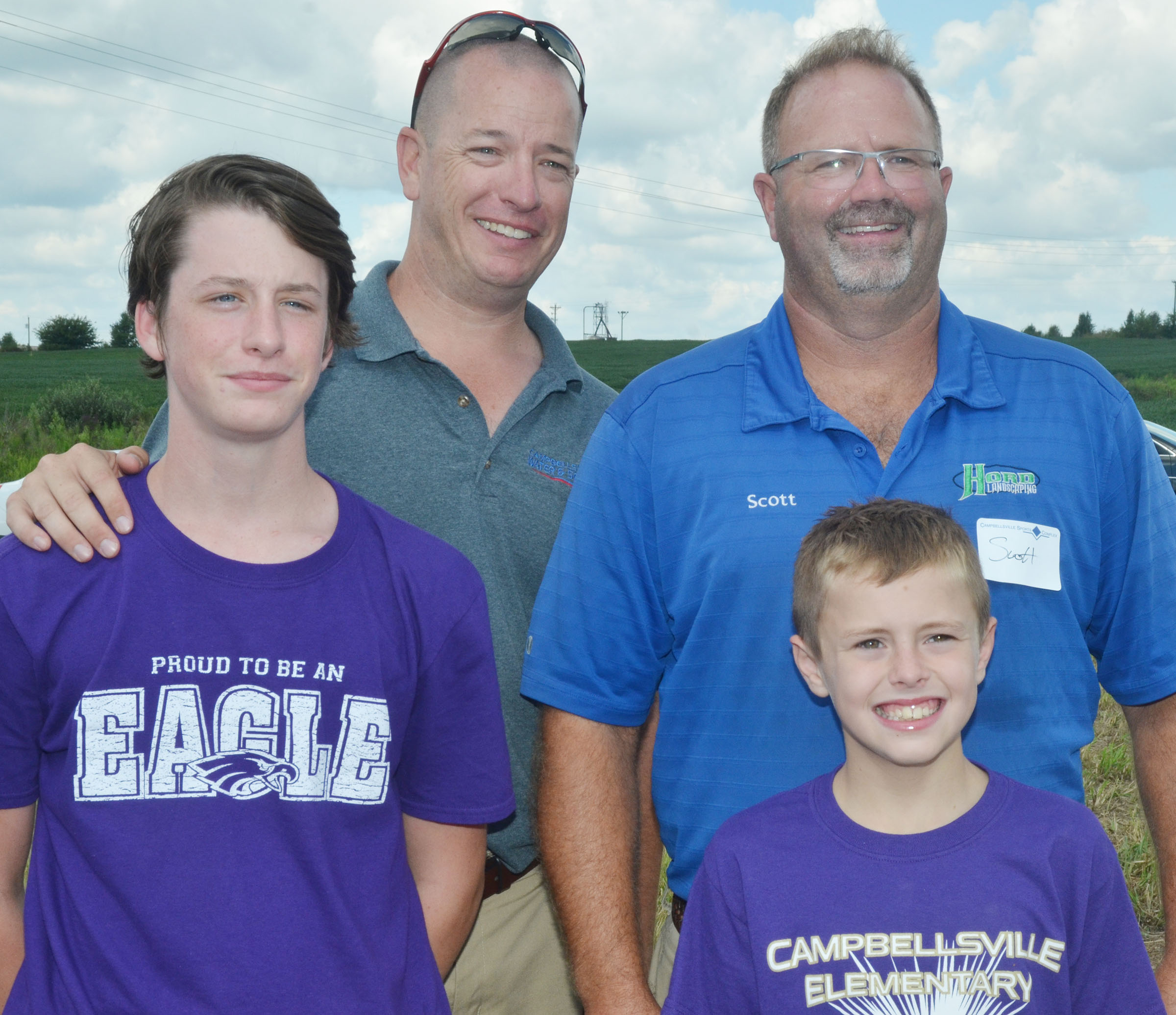CMS seventh-grader Seth Hash, at left, poses for a photo with his father, Griffin, along with fourth-grader Keaton Hord and his father, Scott.