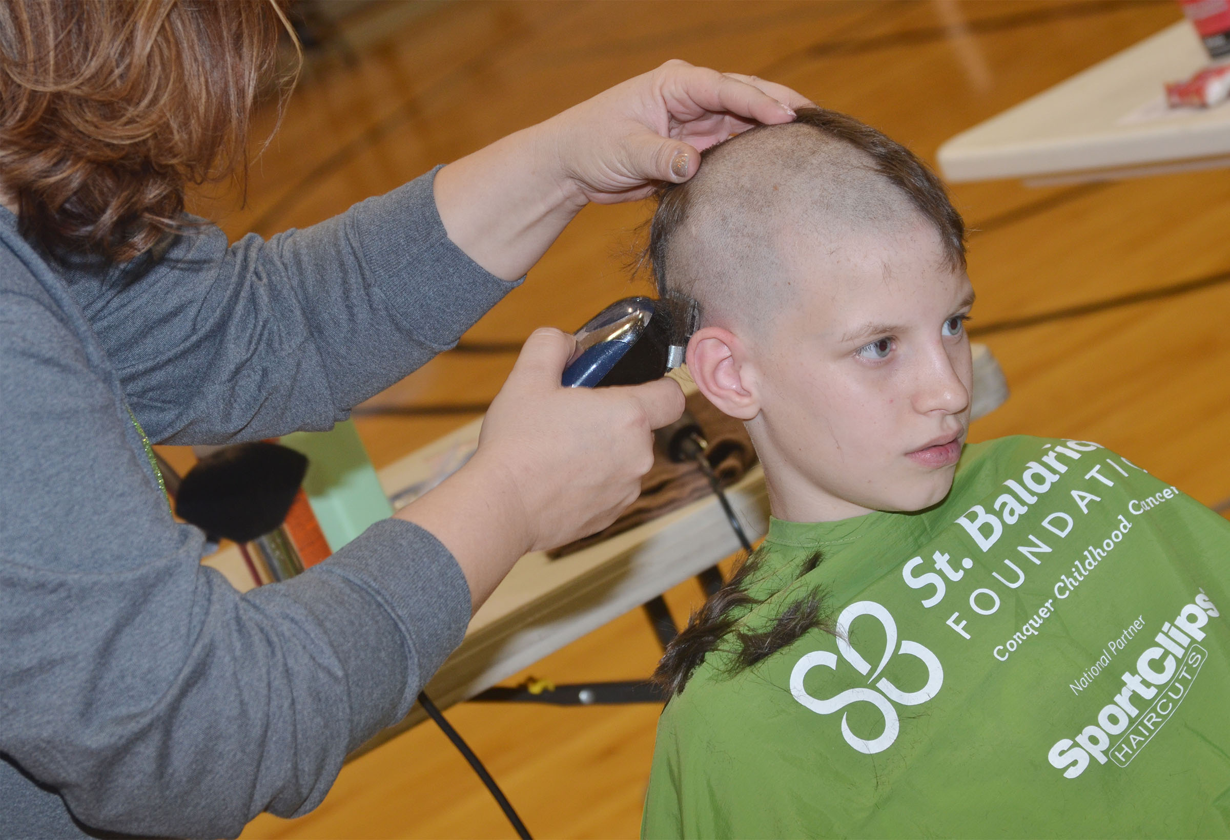 CMS fourth-grader Rowan Petett has his head shaved to raise money for children's cancer research.