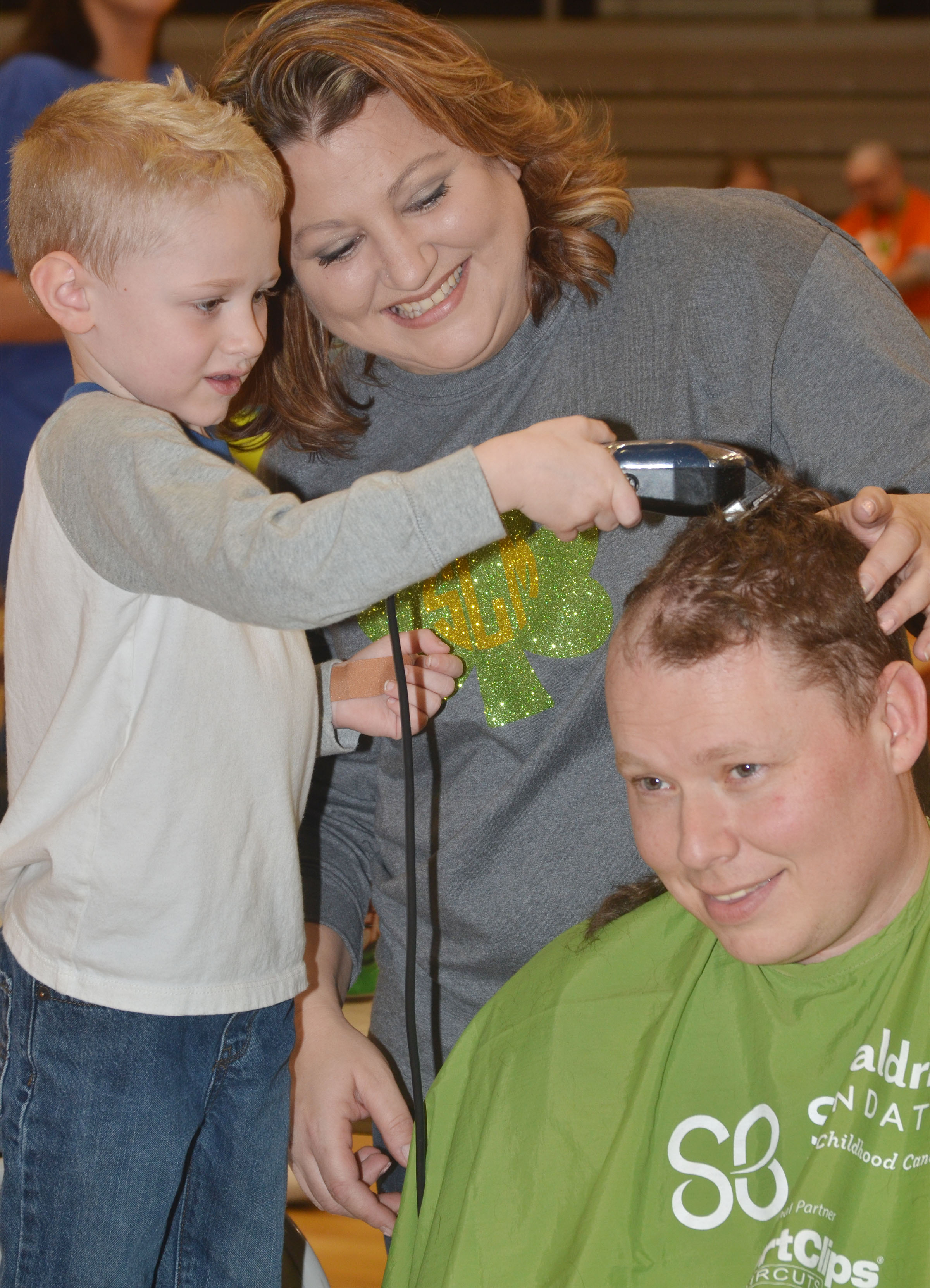 CES kindergartener Jackson Wright shaves his dad Jay's head, with some help from hairstylist Shannon Lawson.