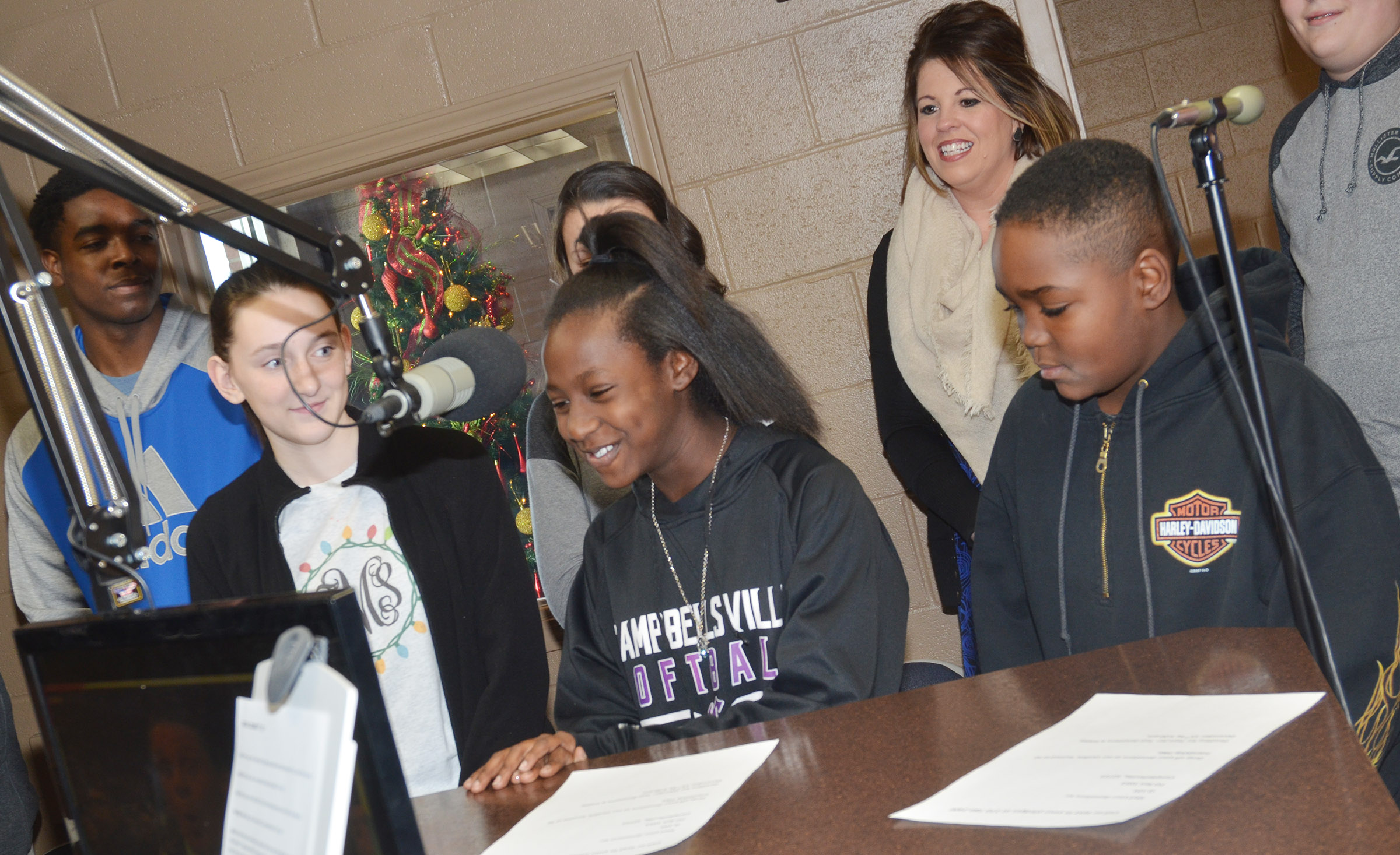 CMS eighth-grader Myricle Gholston, middle, introduces herself on the air.