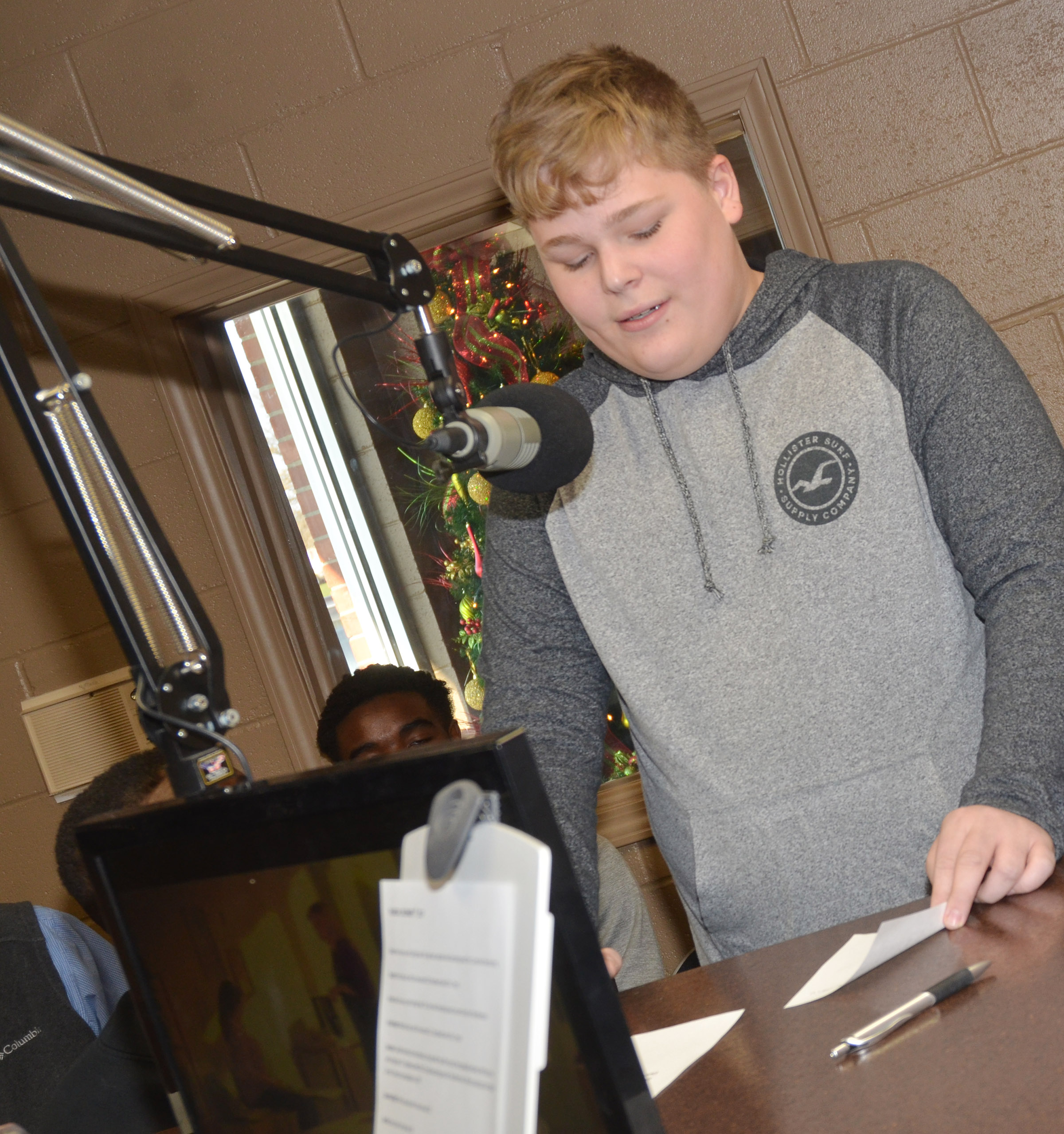 CMS eighth-grader Blake Settle reads a donation to the Toys for Tots drive.
