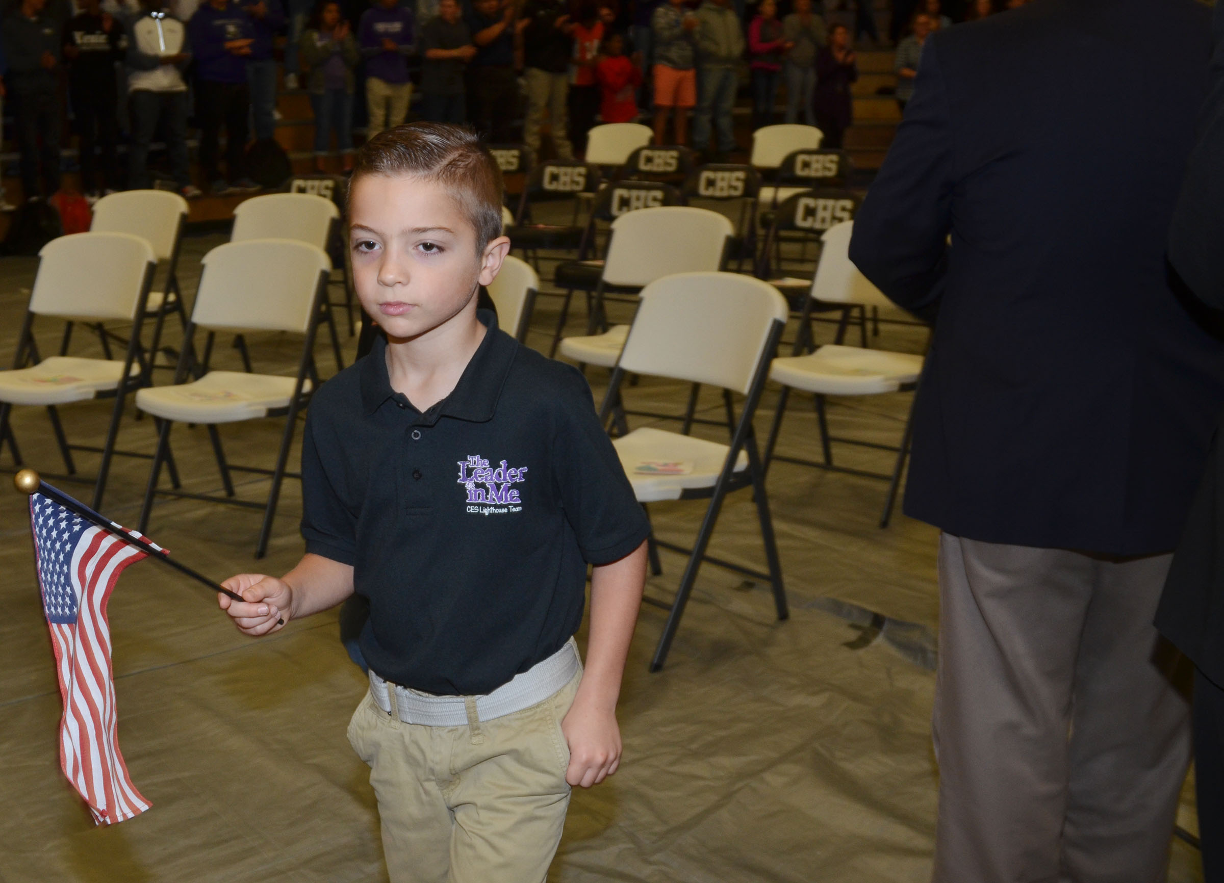 CES third-grader Carson Mills, a member of the school's Lighthouse Team, leads veterans to their seats.