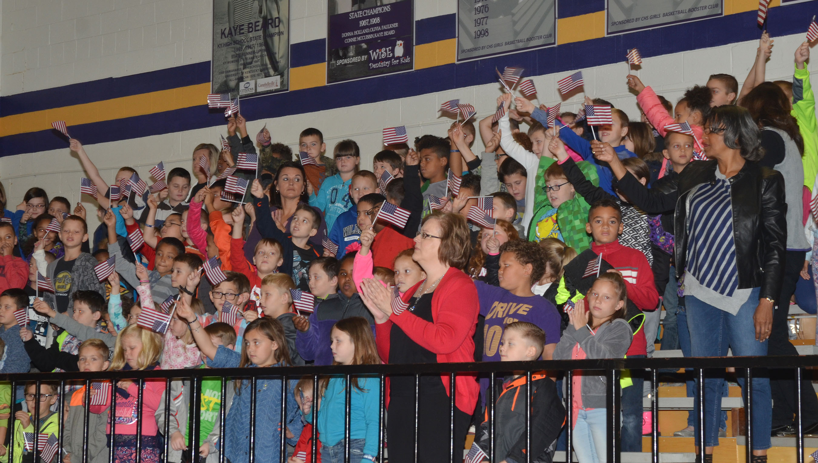 CES students wave their American flags as veterans leave the gymnasium.