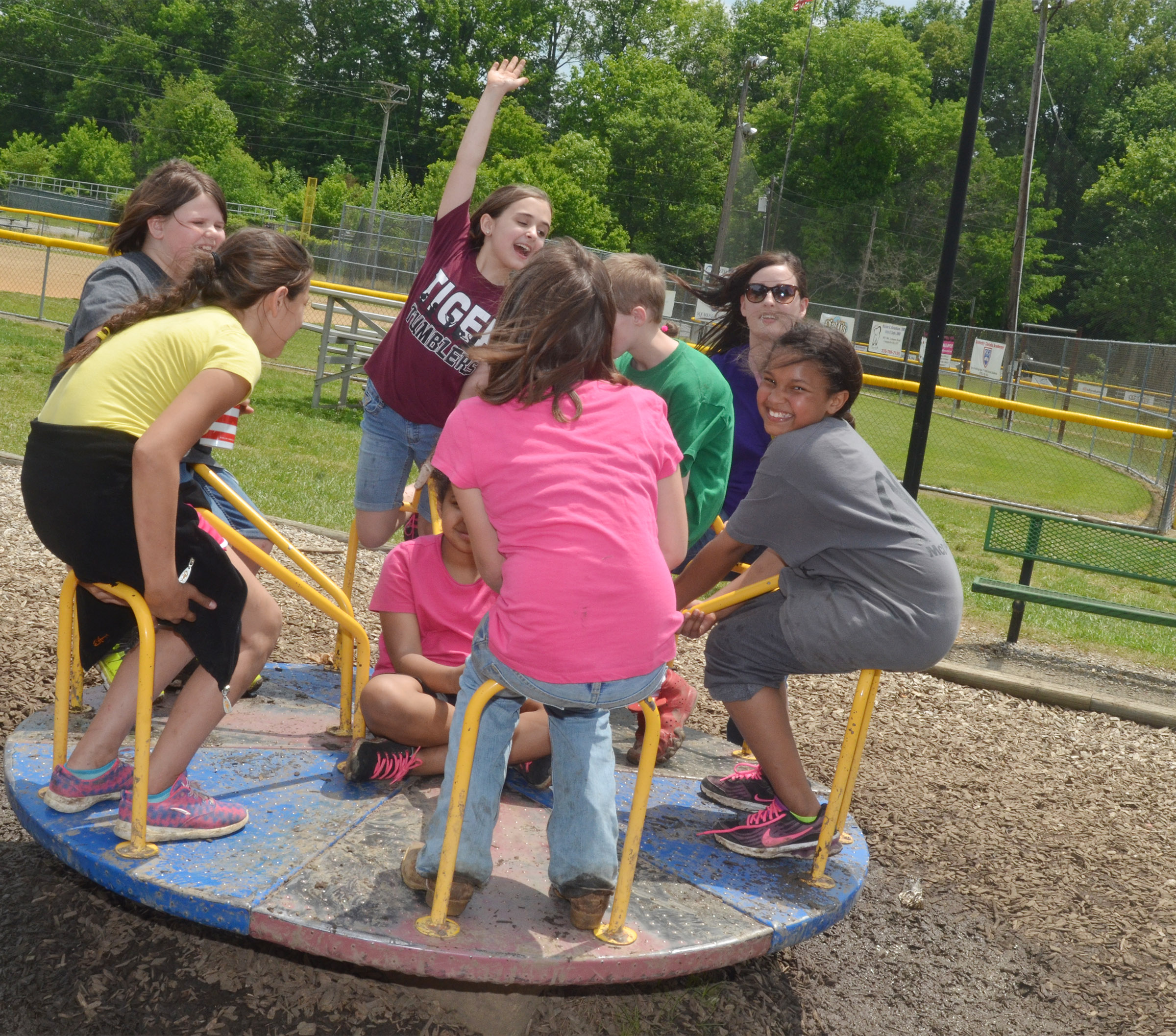 CMS fourth-grader Anna Floyd, center, and her friends laugh as their teacher, Samantha Coomer, pushes them on the merry-go-round.
