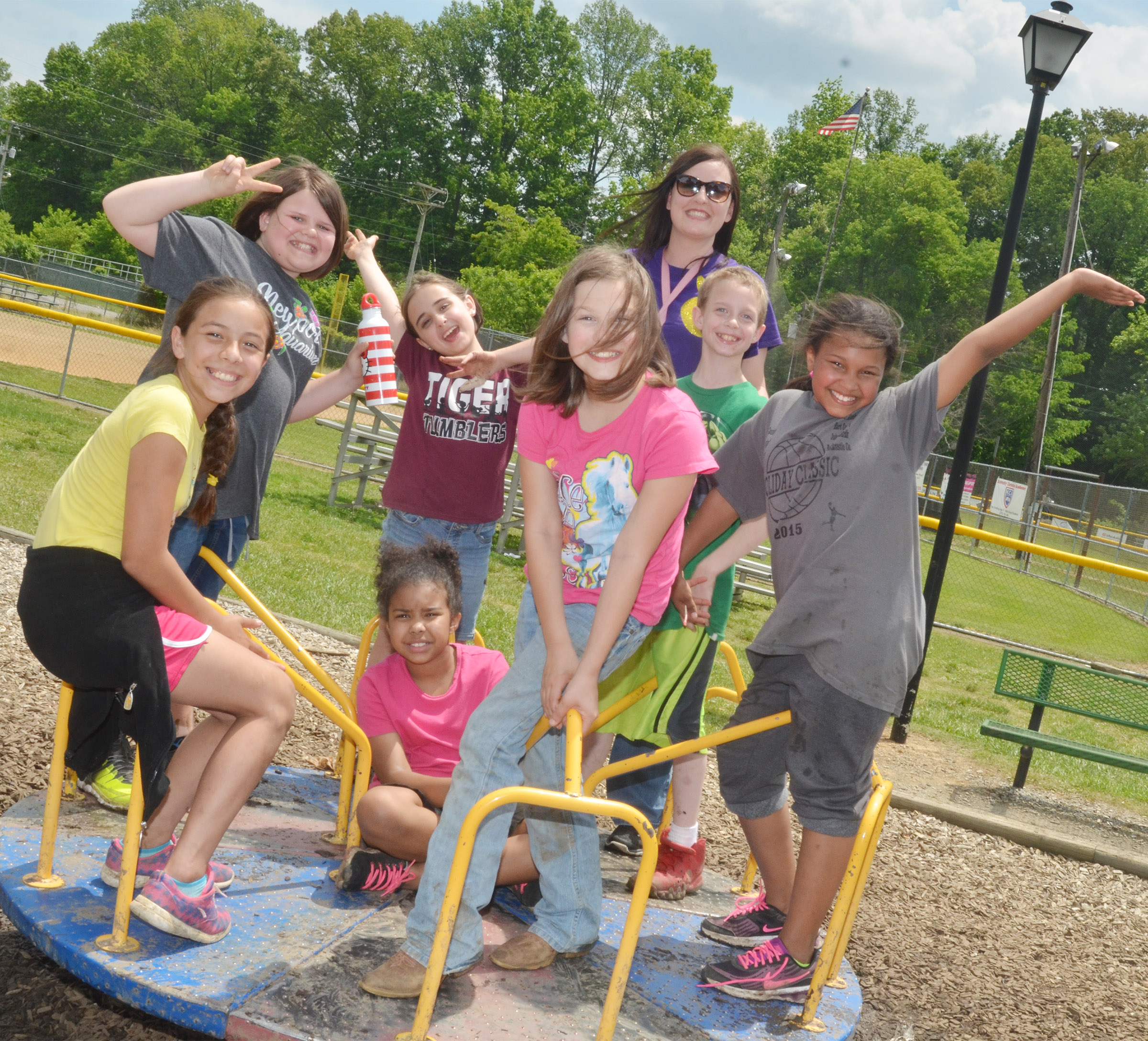 CMS fourth-graders, from left, Marissa Segura, Keeley Dicken, Anna Floyd, Serenity Mings, Destiny Milby, Will Wooley and Jaclyn Jackson smile for a photo on the merry-go-round with their teacher, Samantha Coomer, in back.