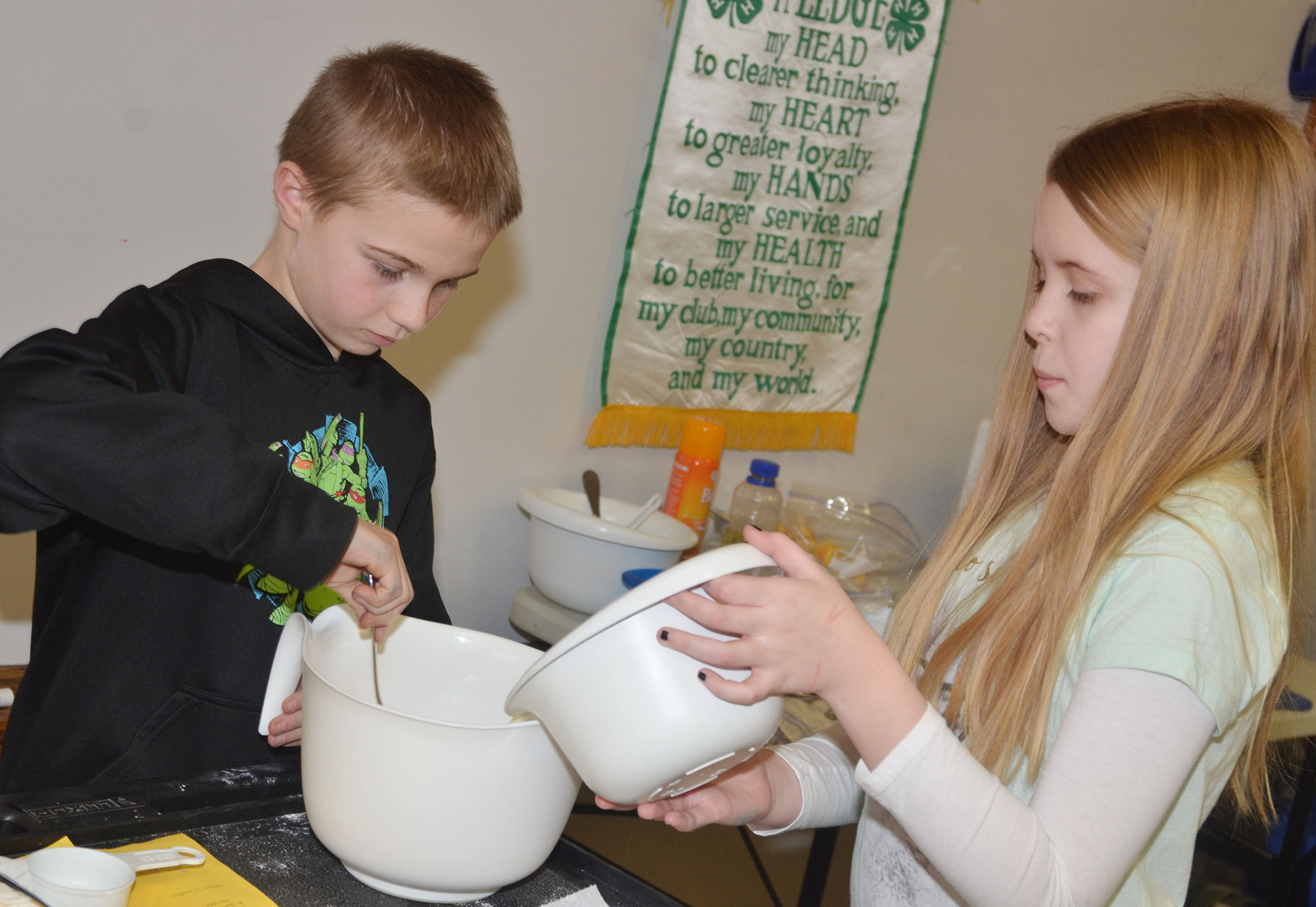 CMS fifth-graders Ethan Cox, at left, and Jaylie Moore mix ingredients.