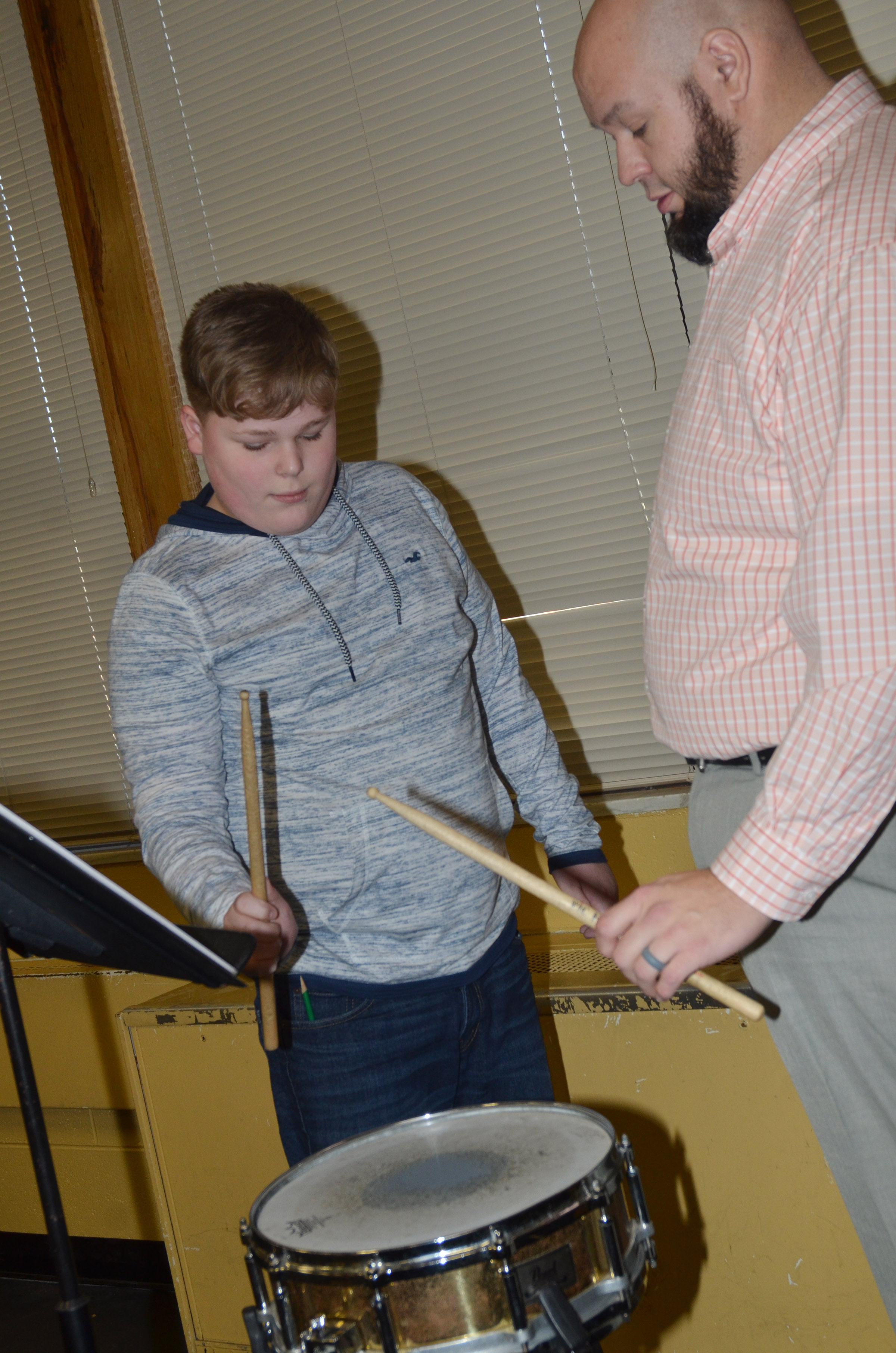 CMS seventh-grader Blake Settle learns to play the drums with band director Zach Shelton.