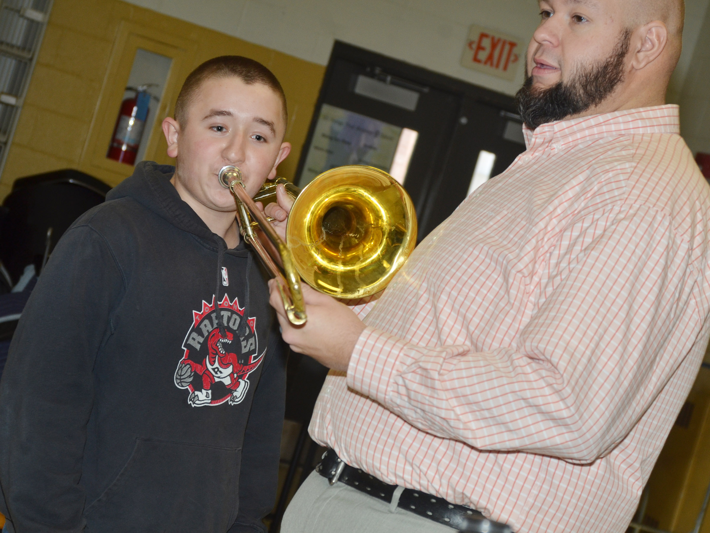 CMS seventh-grader Zachary Shaw plays the trombone with band director Zach Shelton.