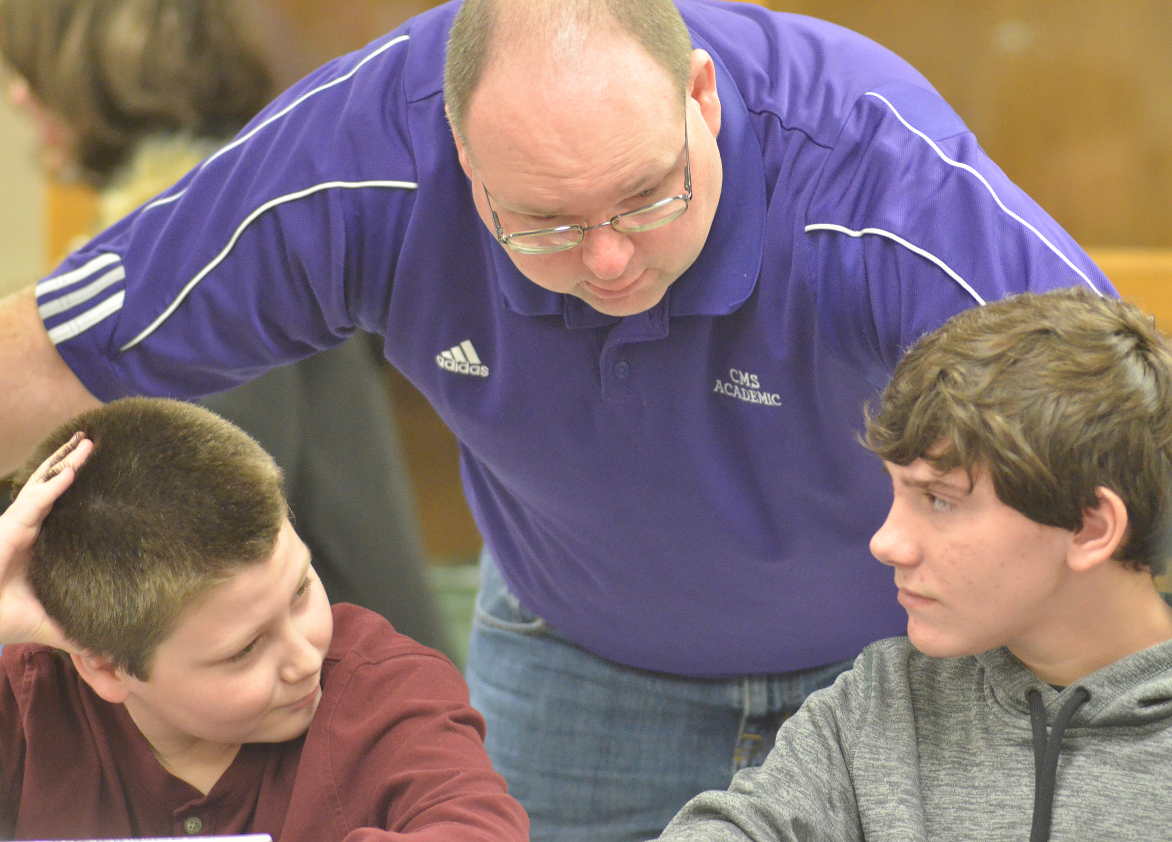 CMS academic teach coach Steven Gumm talks to seventh-graders Bailey Stearman, at left, and Peyton Dabney before a quick recall match.