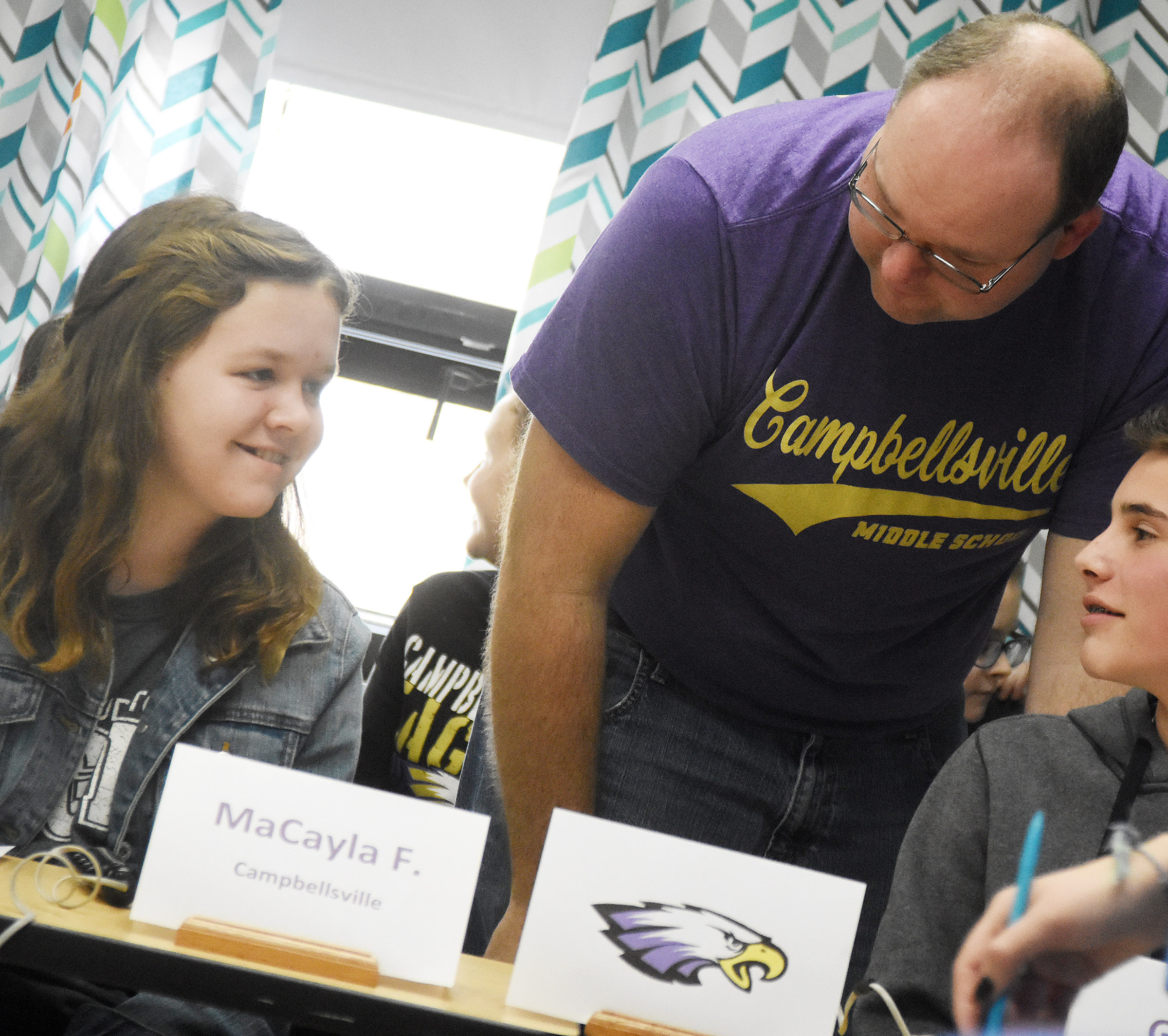 CMS academic team coach Steven Gumm talks to seventh-grader MaCayla Falls, at left, and sixth-grader Isaac Garrison during a quick recall match.